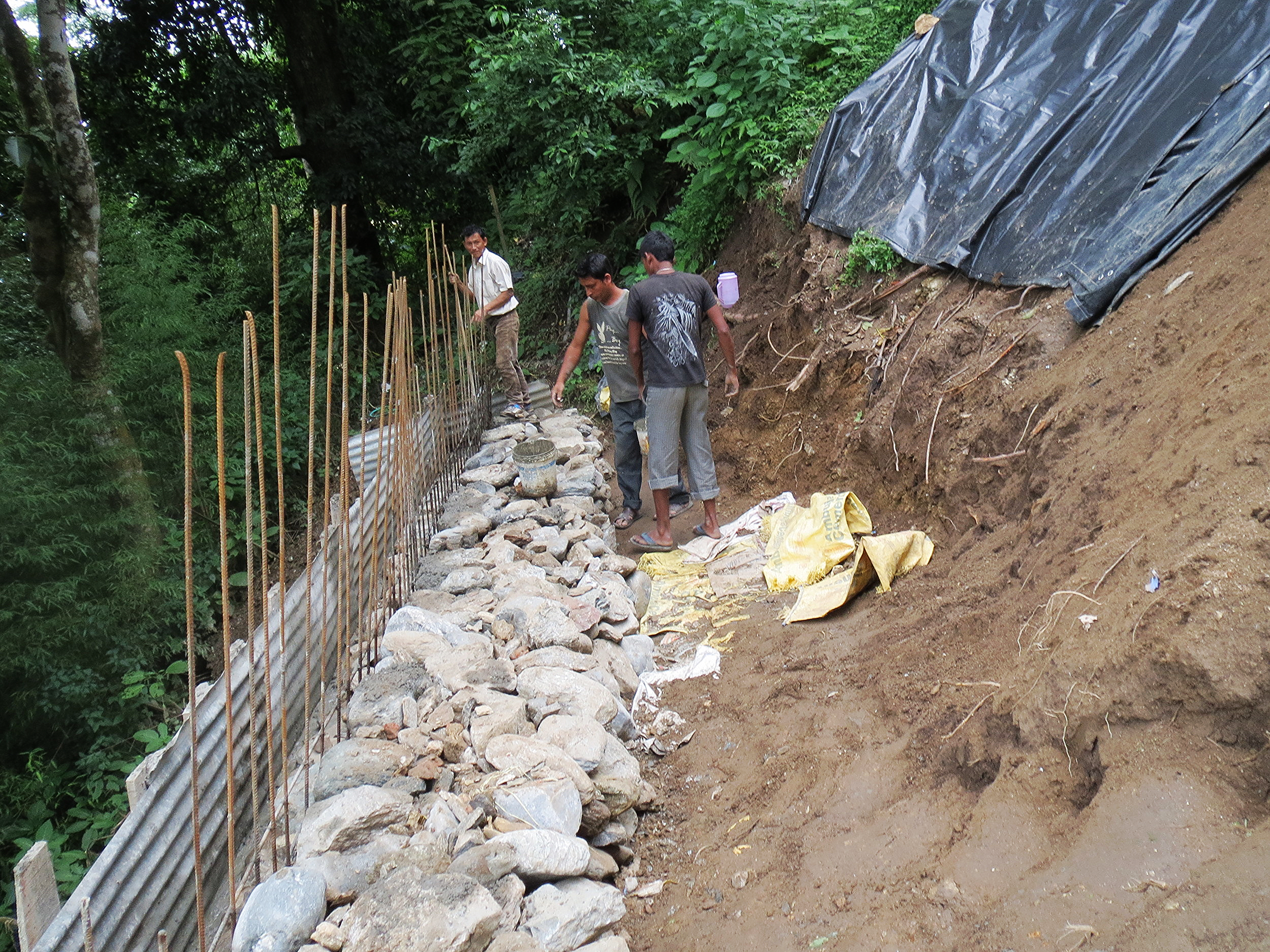 Construction of a retaining wall below the Kalimpong 1 home. Rain caused a large landslide on the slope below the home.