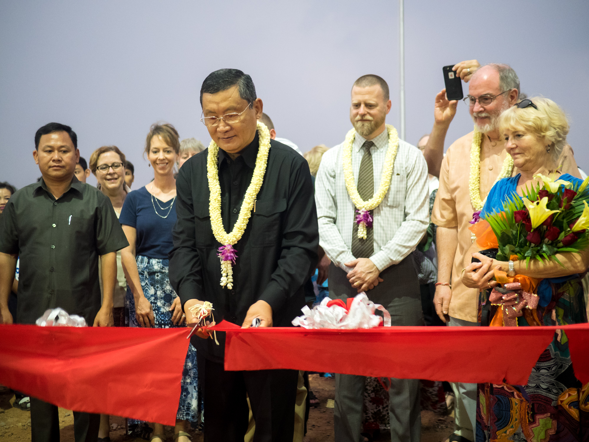 The governor of Battambang Province cuts the ribbon at the Asia's Hope secondary school dedication.