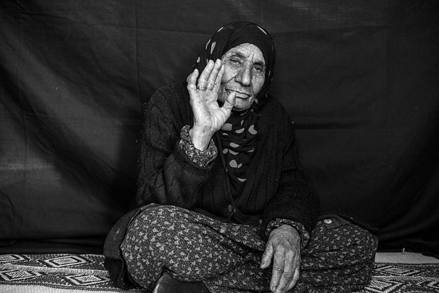 Salma, whose age is somewhere between 90 and 107 according to family members, poses for a portrait in Domiz refugee camp in the Kurdistan Region of Iraq