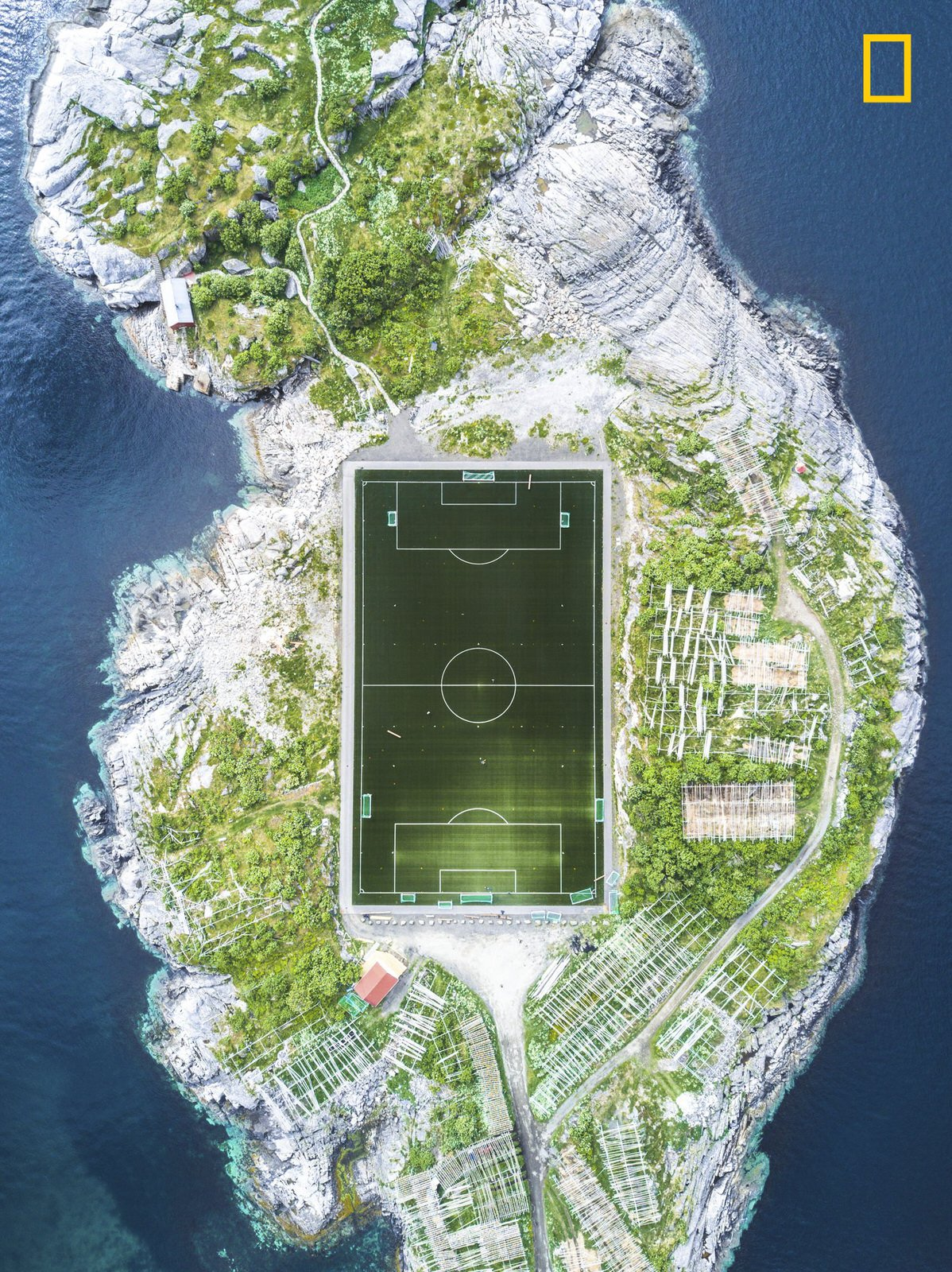 "3rd Place. Photo and caption by Misha De-Stroyev/ National Geographic Travel Photographer of the Year.  Henningsvær Football Field . ""This football field in Henningsvær in the Lofoten Islands is considered one of the most amazing fields in Europe, and maybe even in the world. The photo was taken during a 10-day sailing trip in Norway in June 2017. We arrived at Henningsvær after a week of sailing through the cold and rainy weather. Upon our arrival, the weather cleared up. I was really lucky that the conditions were suitable for flying my drone, and I managed to capture this shot from a height of 120 meters."""