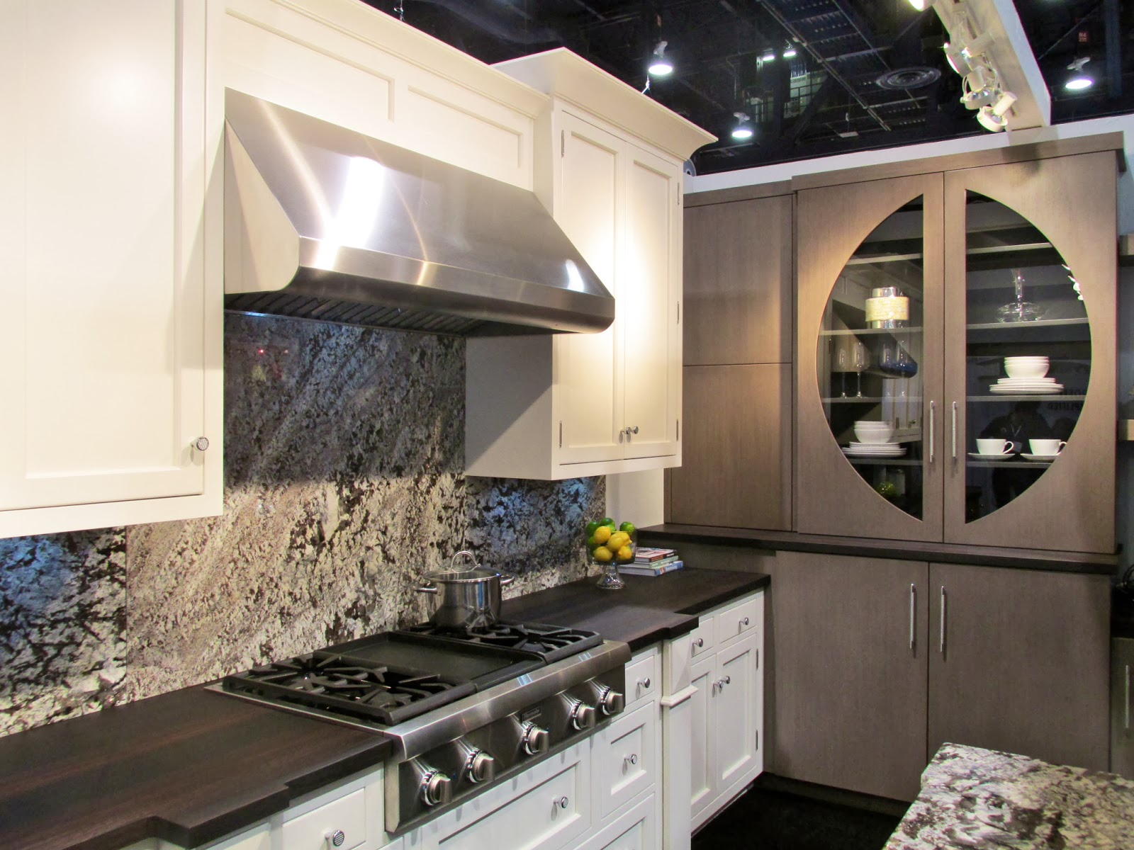 Mixing painted & stained cabinets has moved from trend to a classic look. We liked the dark wood countertops that tie these two pieces together. (Not to mention that striking glass door!)