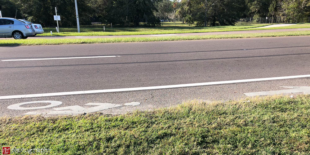 narrowed bike lane because the grass grows over the pavement