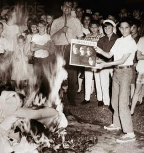 A kid about to burn his Beatles record at a bonfire.