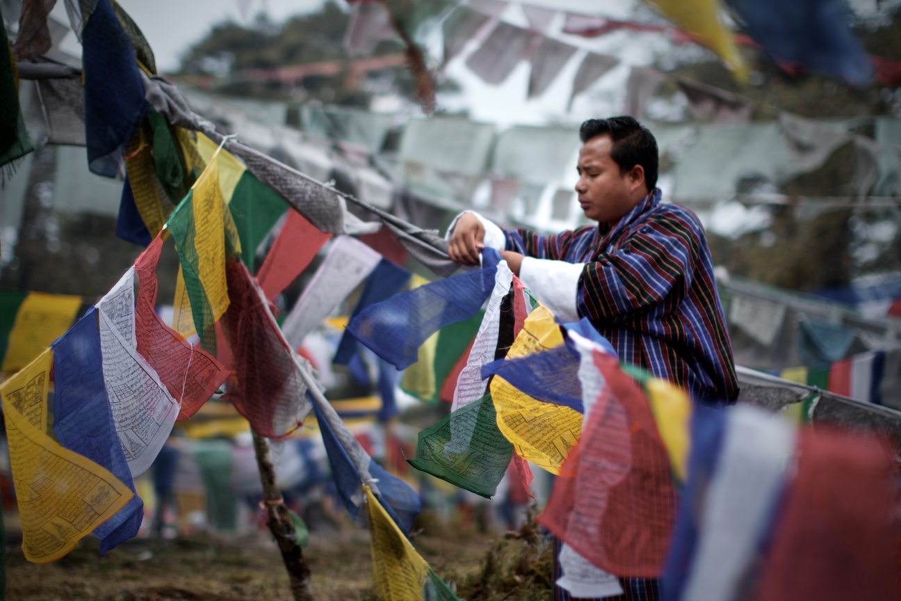 Nima showing us how to hang prayer flags and reciting a pray for us.