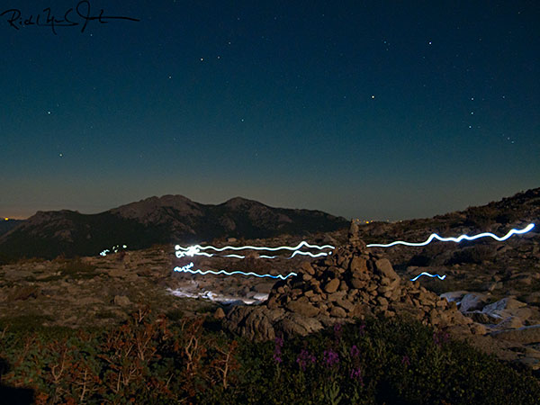 3:04 AM: Headlamps of hikers appear like giant fireflies as they pass a stela marking the route to the summit of Long's Peak. Orion's Belt (three equally-spaced stars in a vertical line) floats above the horizon at right.