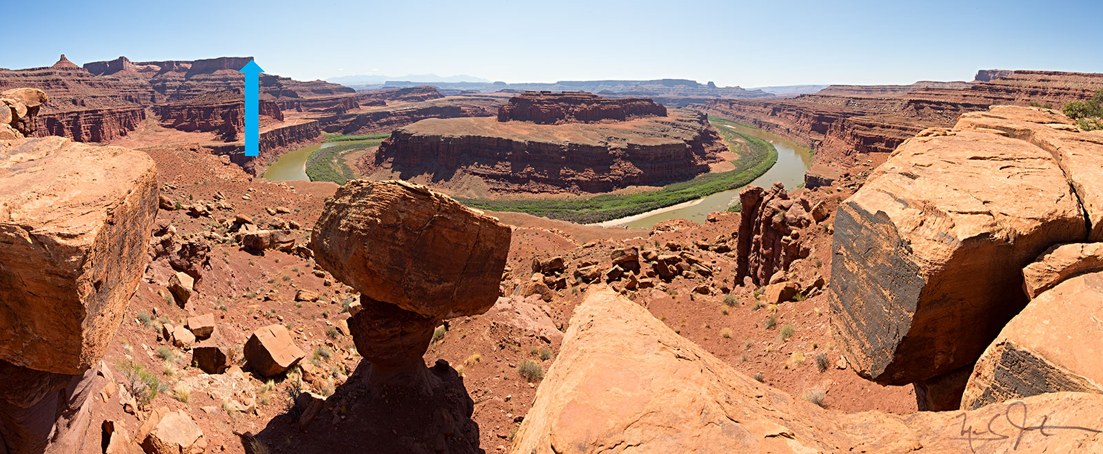 From the northwest side of the Gooseneck, down on the White Rim Trail.  The point of view of the image above is indicated by the blue arrow.