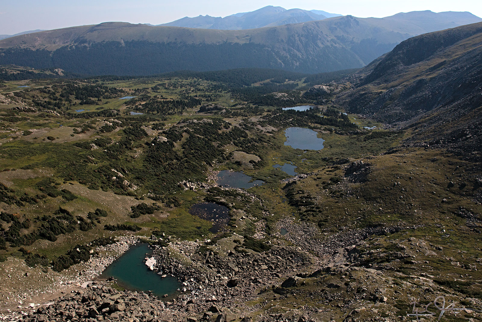 Looking from the Continental Divide over a few unnamed lakes towards Forest Canyon, with Trail Ridge and Trail Ridge Road in the distance.