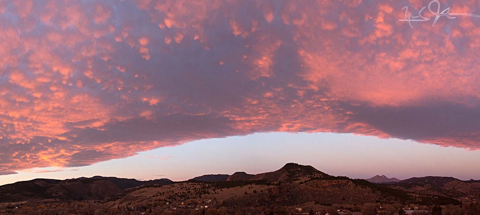 Sunrise illuminates clouds over the Continental Divide from the vicinity of Lyons, CO.