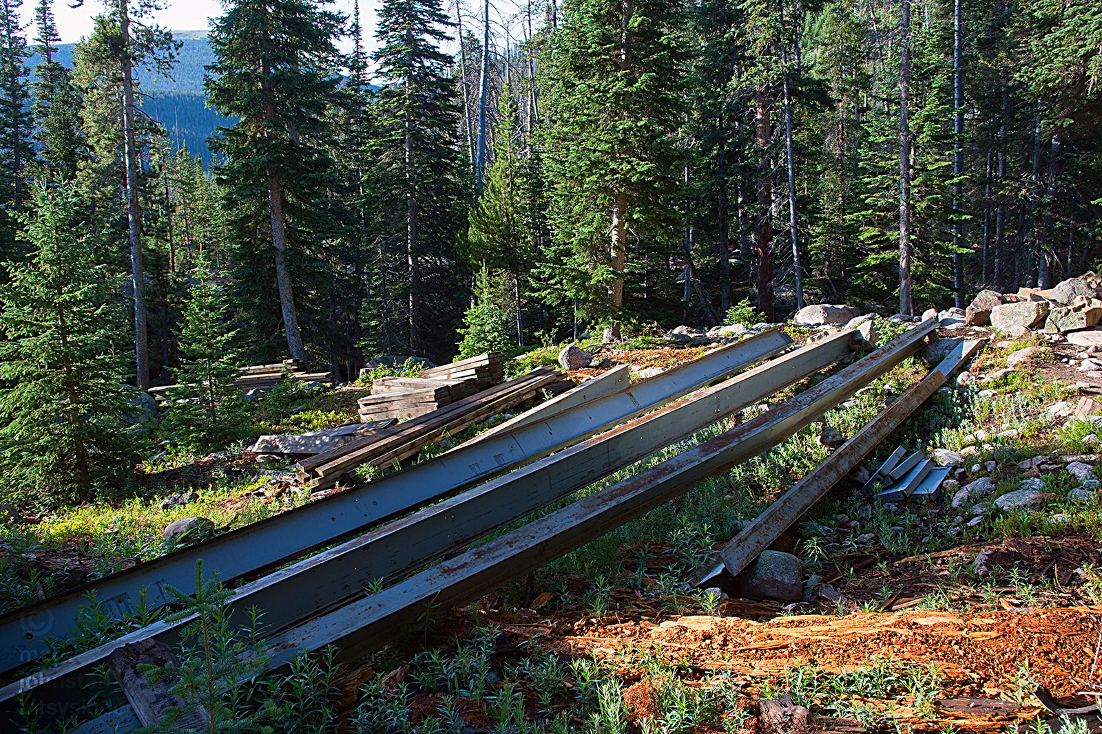 New i-beams and decking planks positioned for a rebuild of the bridge to cross Ouzel Creek.