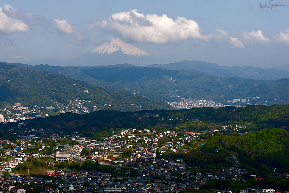 The Japanese city of Ito [伊東, pop 70K] in Shizuoka Prefecture[静岡県], lies on the coast of the mountainous Izu Penninsula [伊豆半島]. In this view looking roughly north from Komuroyama[小室山], Mt. Fuji [富士山], elevation 3776 m, can be seen 35 mi [58km] distant. From this point, central Tokyo is about 61 mi [98 km] away, a little out of the right side of the frame in this photo.