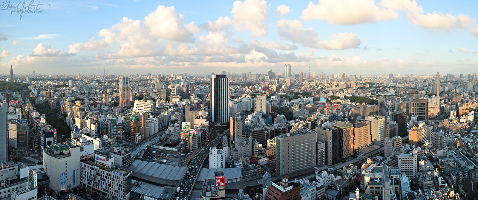 """Tokyo's Shibuya district. The shiny cylinder just right of center in the distance is Roppongi Hills, with red-and-white Tokyo Tower just to its right. The famous """"Shibuya Scramble"""" intersection is the area with the white bands painted on the street at the lower left. There is an airplane on the roof of a building at lower right."""