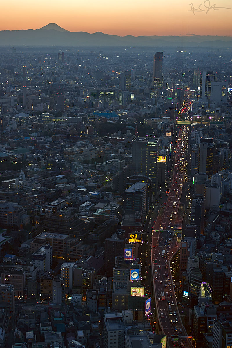 As the sunset fades behind Mt. Fuji some 60 miles distant, the lights come up in Tokyo's western districts of Roppongi and Shibuya.