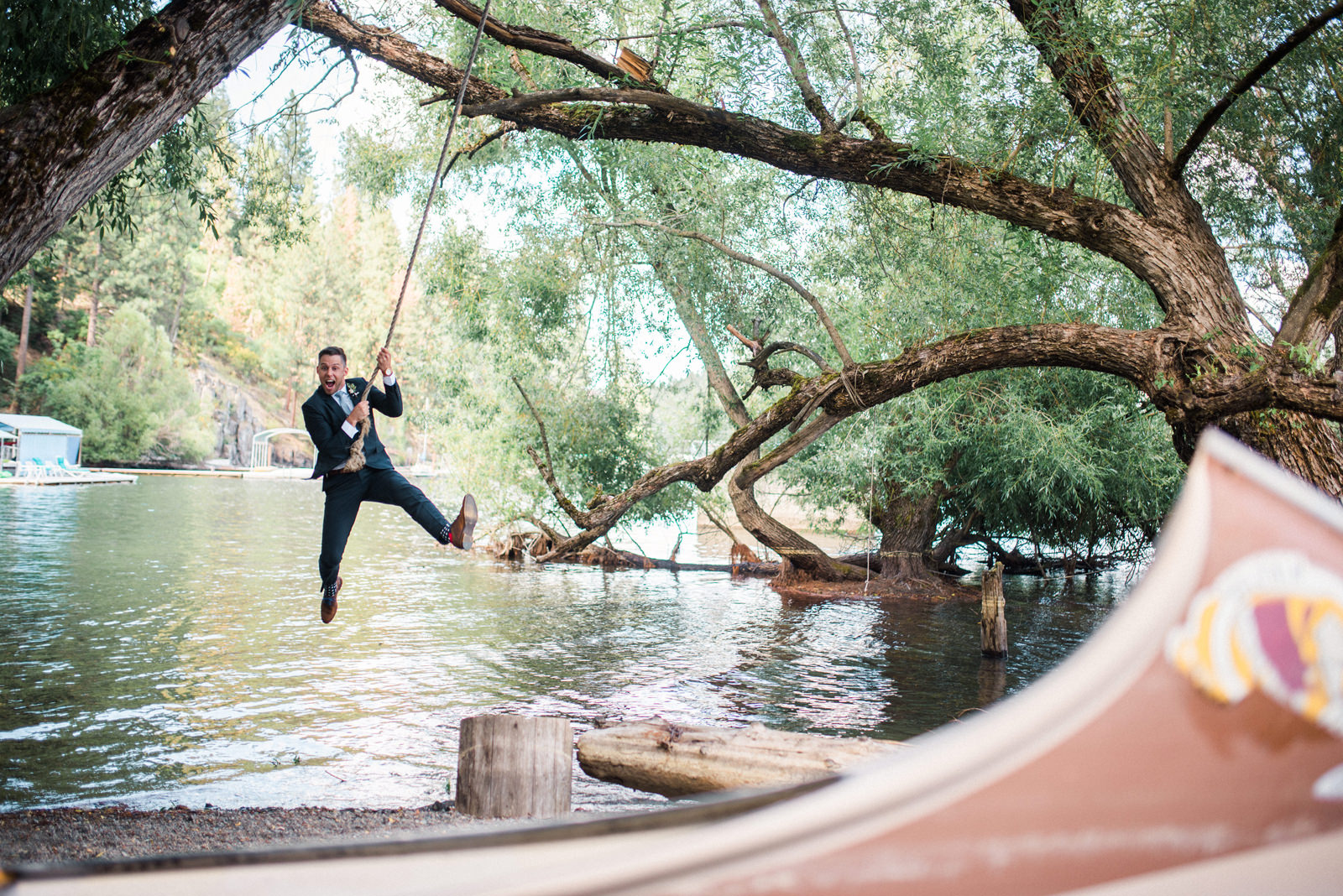 060-groom-swinging-on-rope-swing-near-a-canoe-in-coeur-d-alene-idaho.jpg