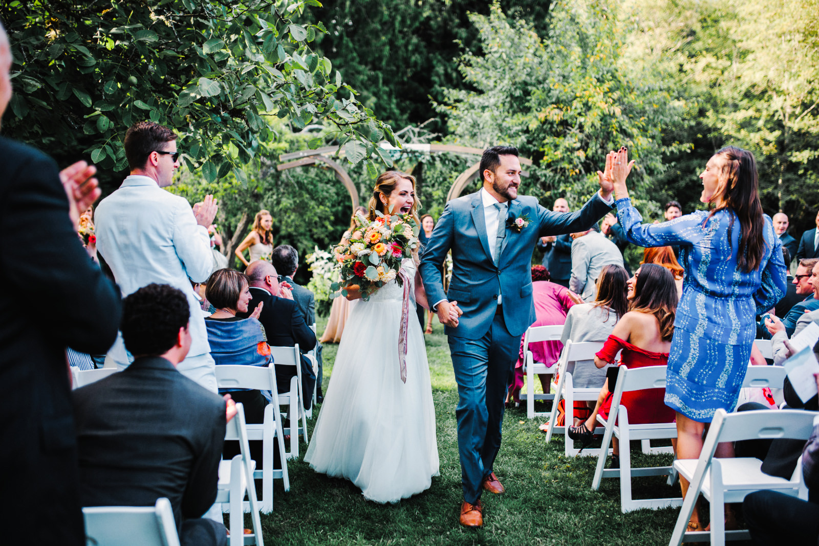 240-the-farm-kitchen-wedding-with-bride-and-groom-high-fiving-guests.jpg
