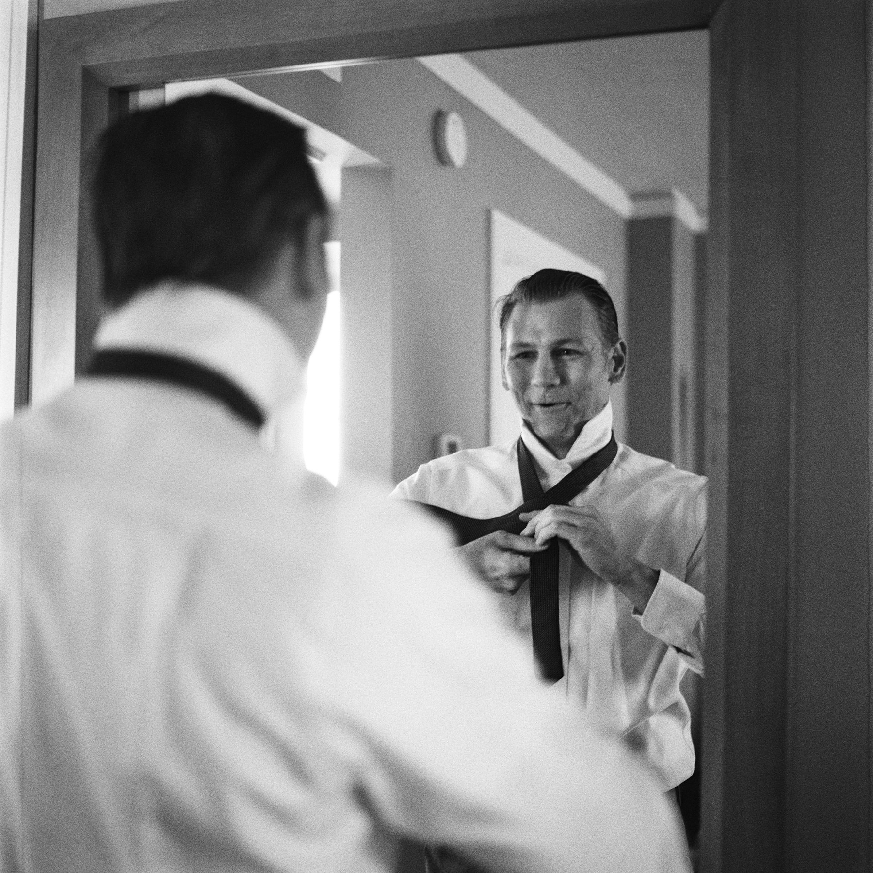 167-groom-finishing-his-tie-and-opening-a-wedding-gift-in-downtown-seattle.jpg