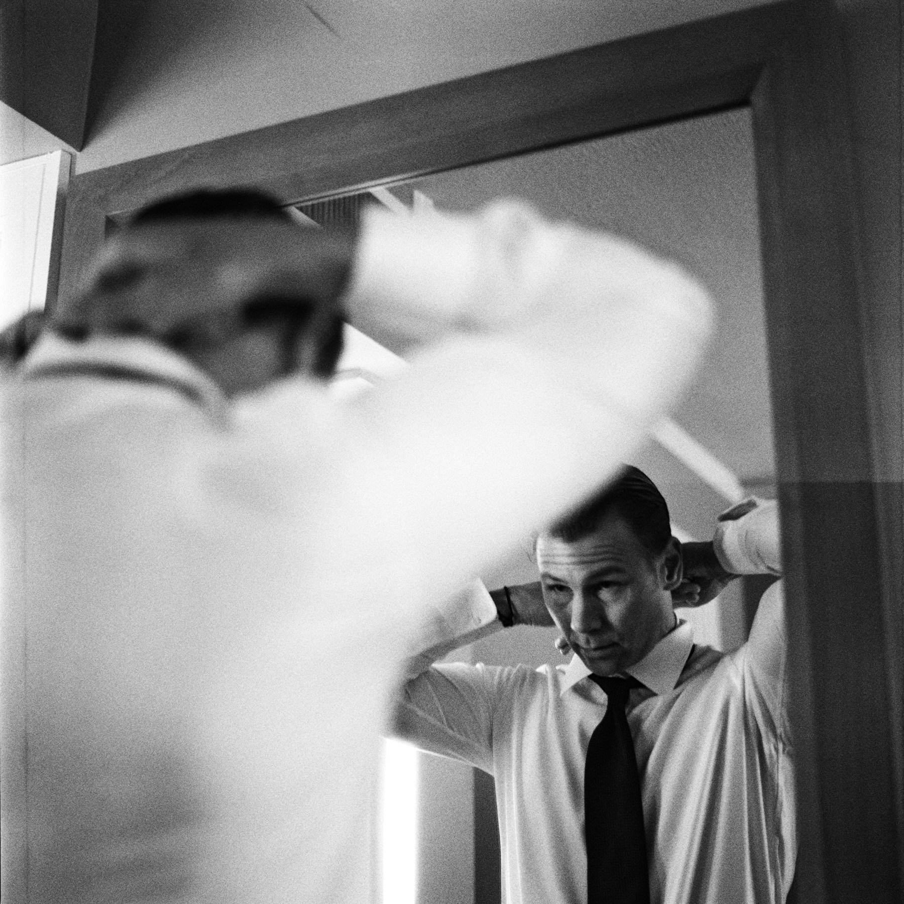 168-groom-finishing-his-tie-and-opening-a-wedding-gift-in-downtown-seattle.jpg