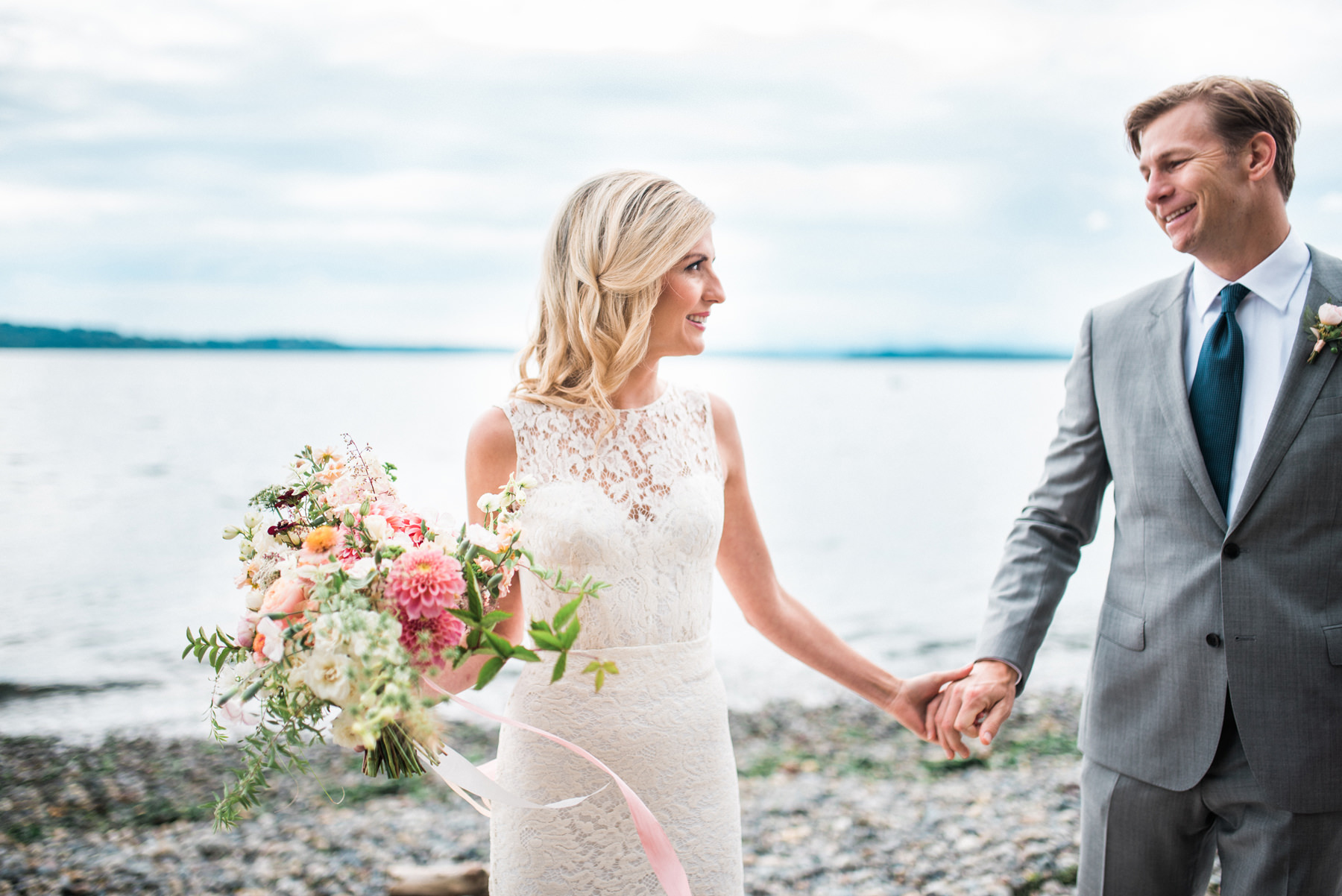 182-wedding-couple-walking-on-driftwood-holding-flowers-by-floret-floral.jpg
