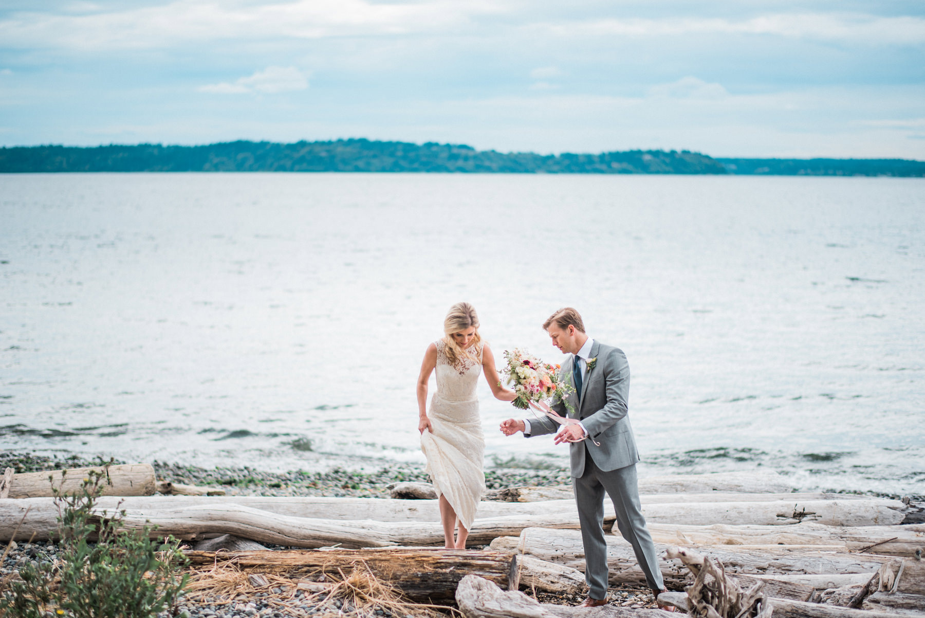 183-wedding-couple-walking-on-driftwood-holding-flowers-by-floret-floral.jpg