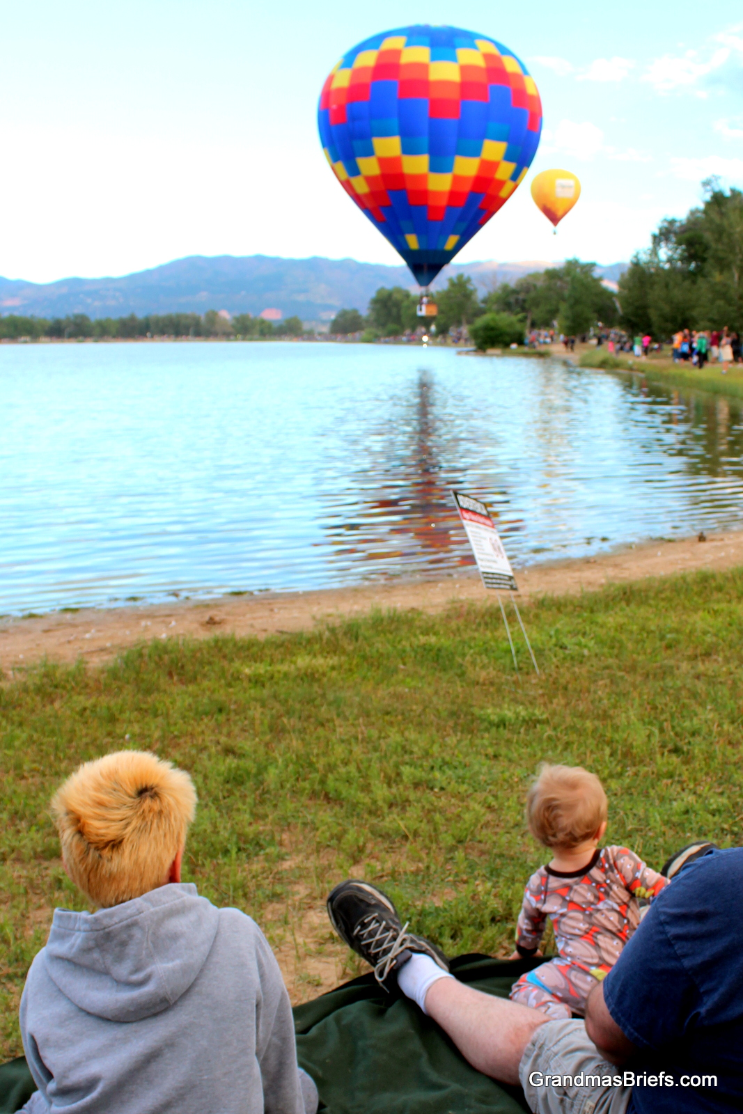 Benjamin watches balloons emerge over treetops, with brother (another b!) james and daddy