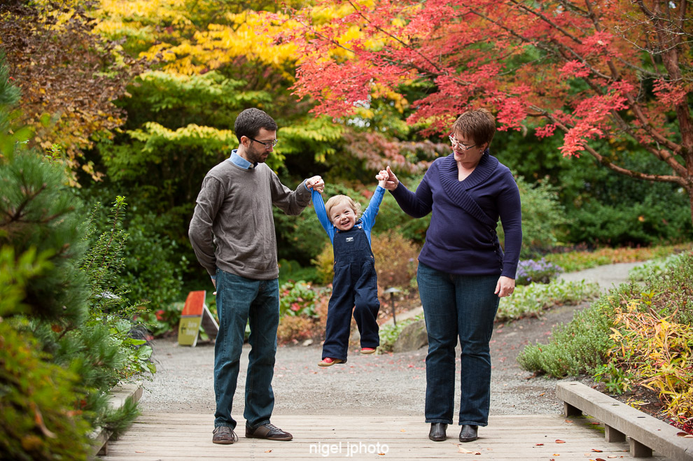 family-of-three-swinging-child-red-fall-colors-seattle-family-photography.jpg