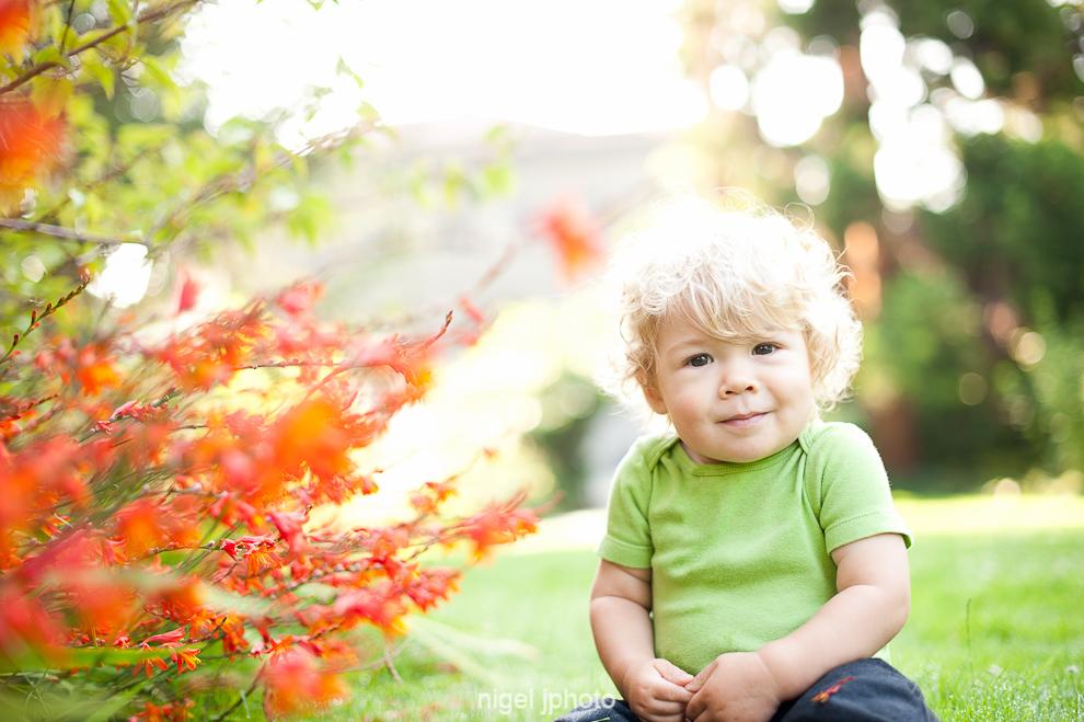 portrait-one-year-old-blonde-boy-sitting-ballard-locks-orange-flowers-seattle.jpg