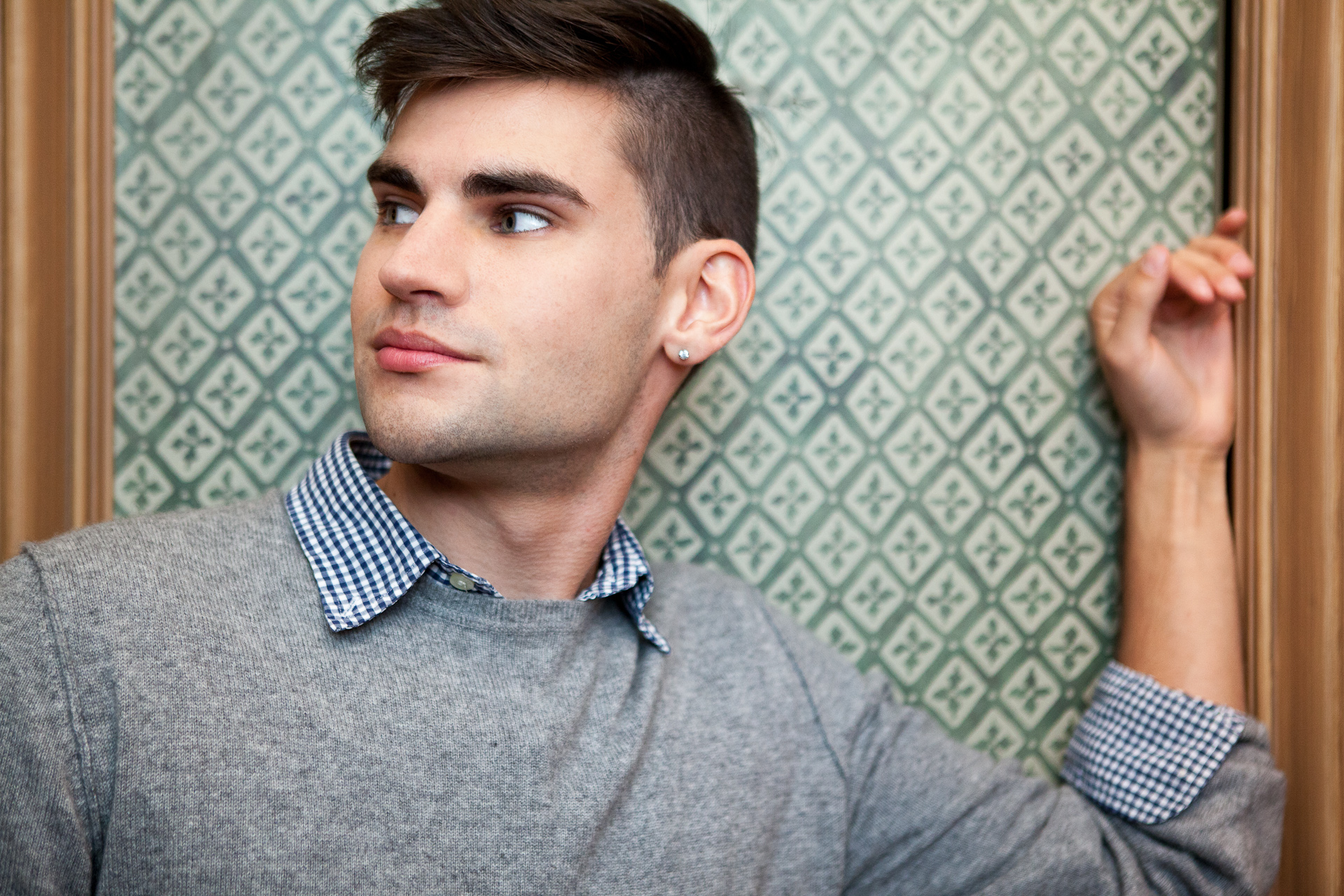 Portrait of a young white man, dressed casually against patterned wallpaper during a shoot in Boston's Beacon Hill Neighborhood.