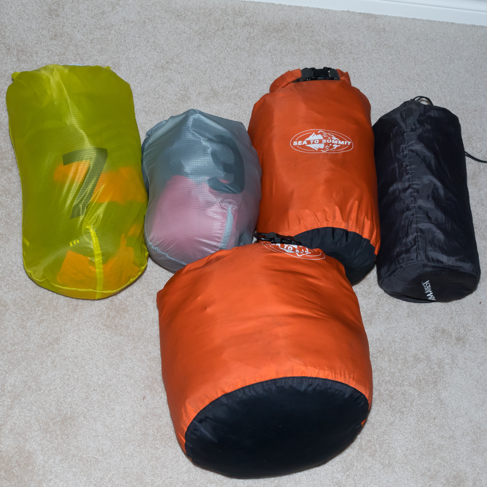 The top four bags fit into my backpack, which in turn fits in my duffel bag. The 7- and 9-liter stuff sacks have clothing. The small Orange dry Bag holds My tent and fly. The black bag is my sleeping pad. The large orange dry bag holds my sleeping bag.