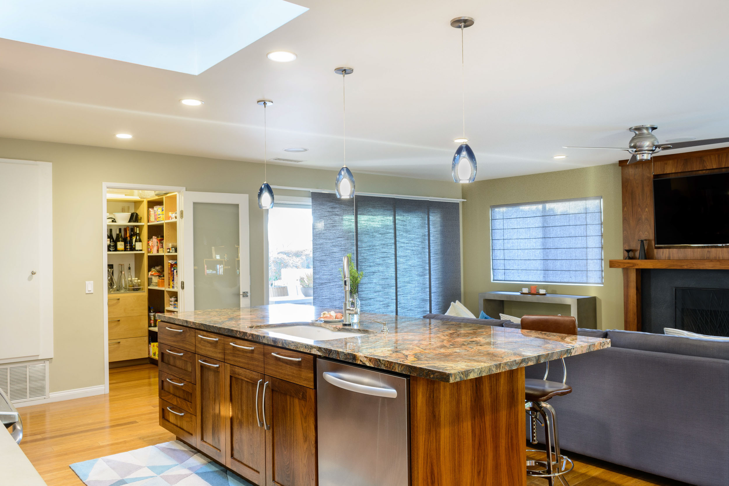 Great room kitchen remodel: the island, set as an anchor in this open floor plan, provides a seamless flow between the kitchen, pantry, living room and patio area