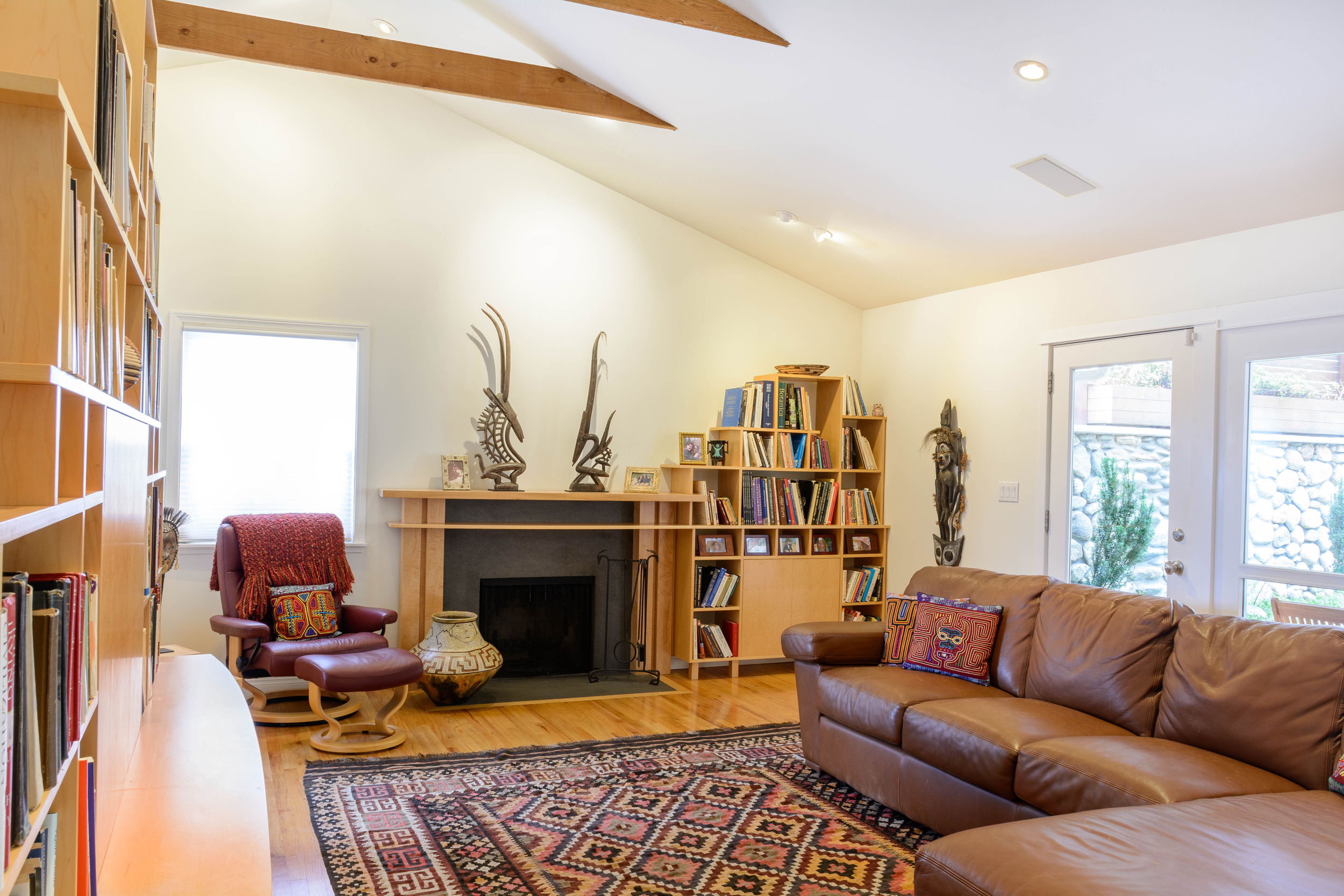 Bright, comfortable and warm living room with cathedral ceiling and exposed structural beams opening onto the backyard