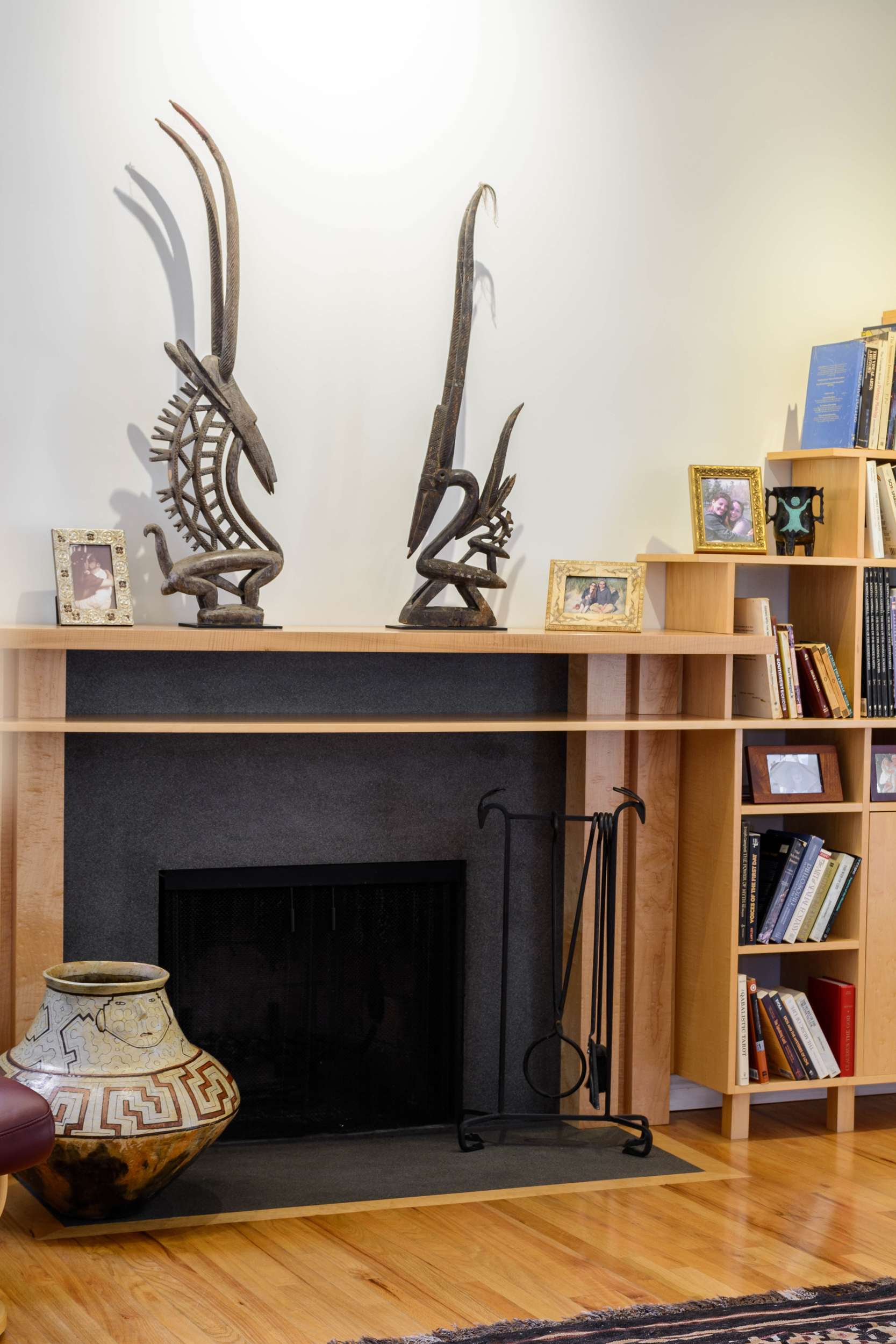 Living room fireplace with absolute black granite and a curved maple mantel which seamlessly transitions with the bookshelves