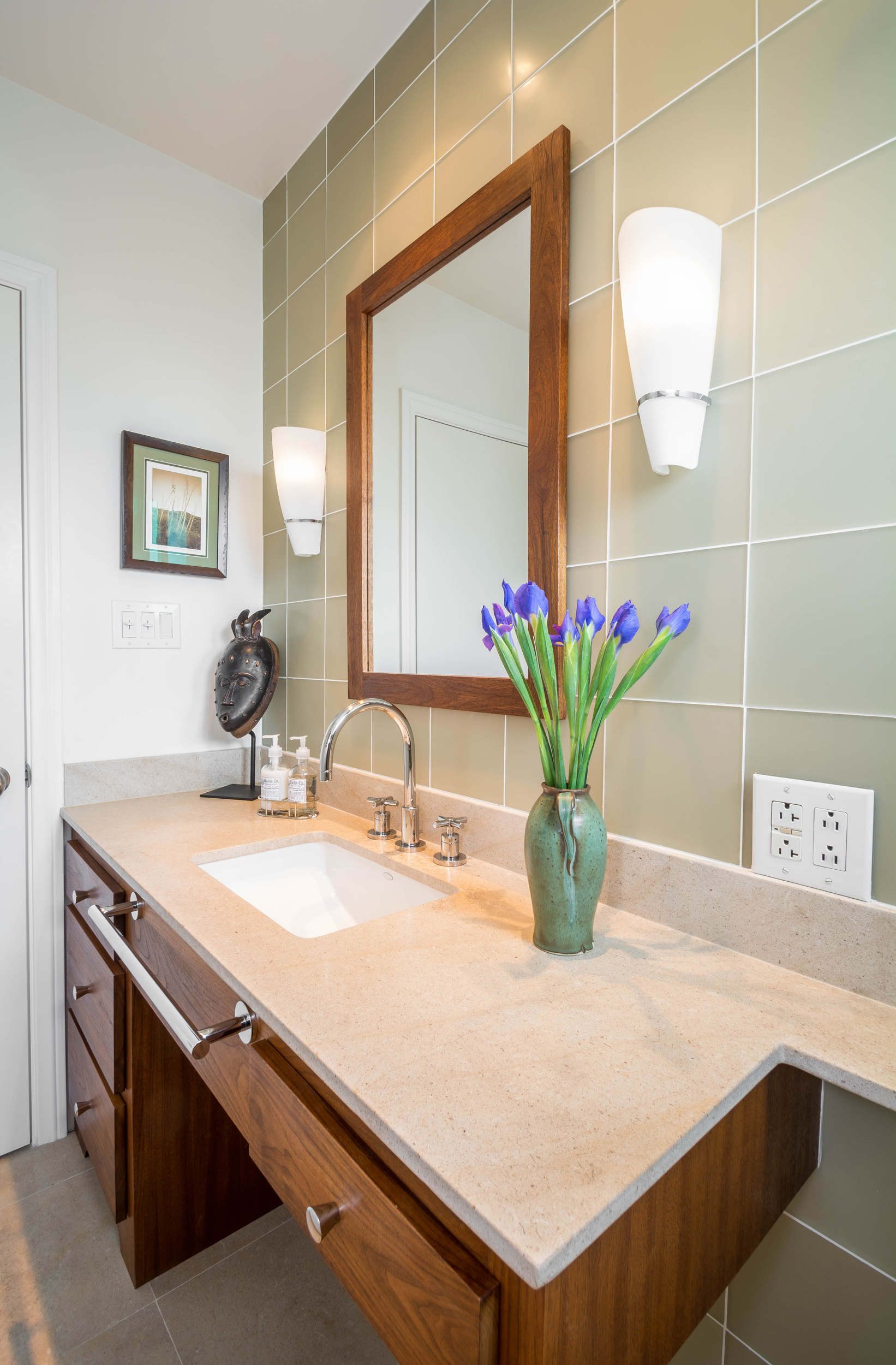 This sophisticated powder room features a custom-built walnut mirror frame and bathroom vanity accentuated by a limestone top, matte glass tiles and modern sconce light fixtures