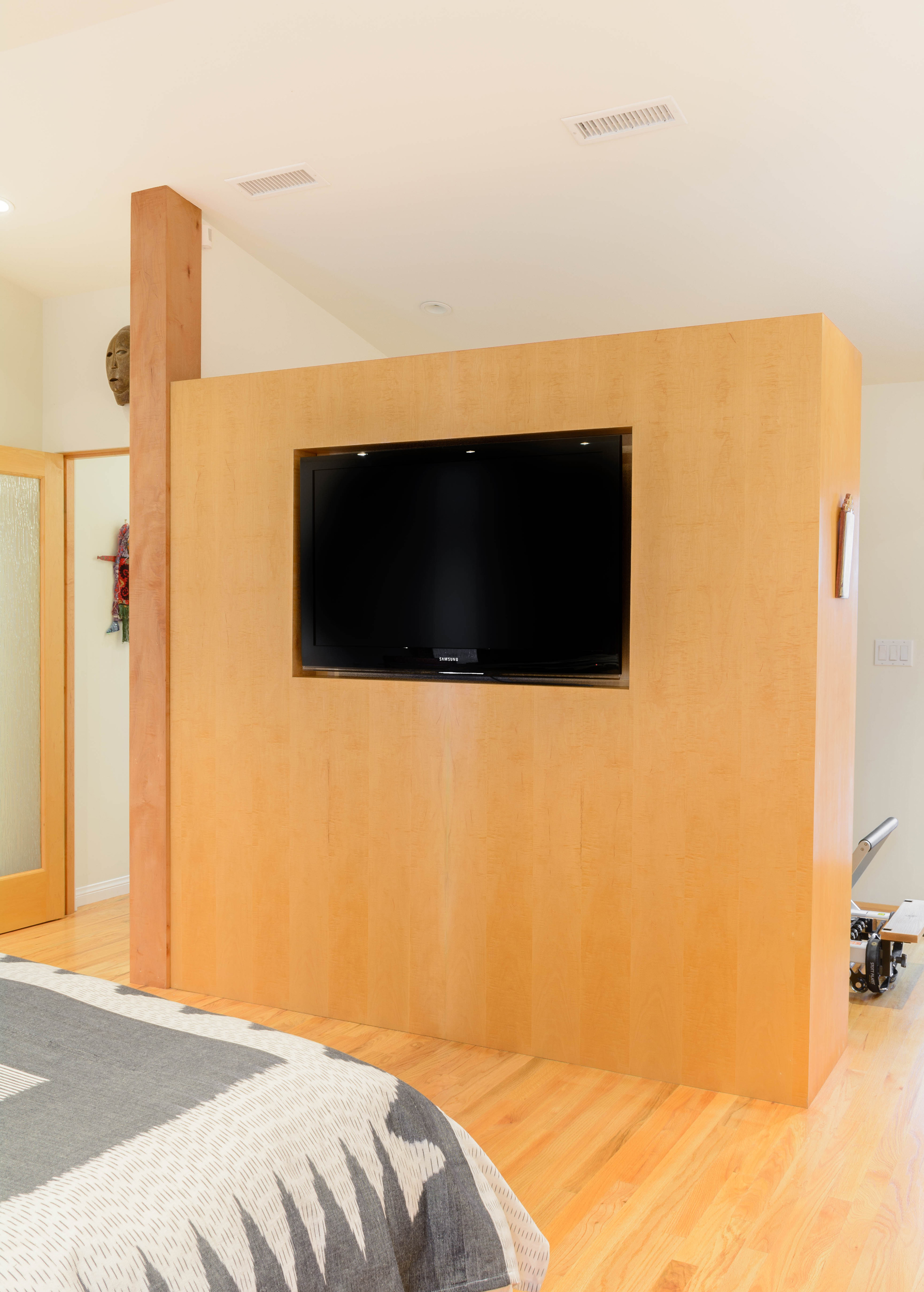 Maple room divider separates the master bedroom from the workout area