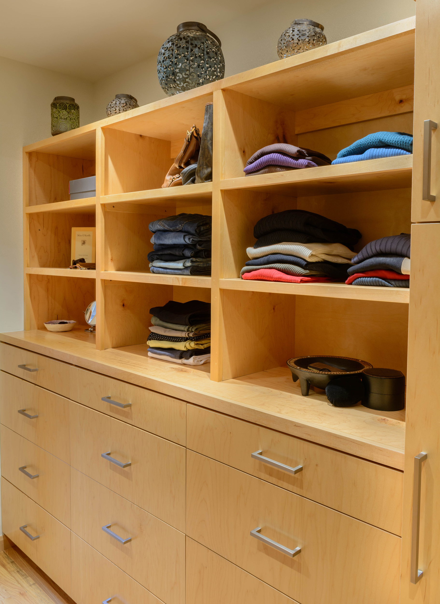 Fingered maple cabinets with drawers and open shelving in this master closet