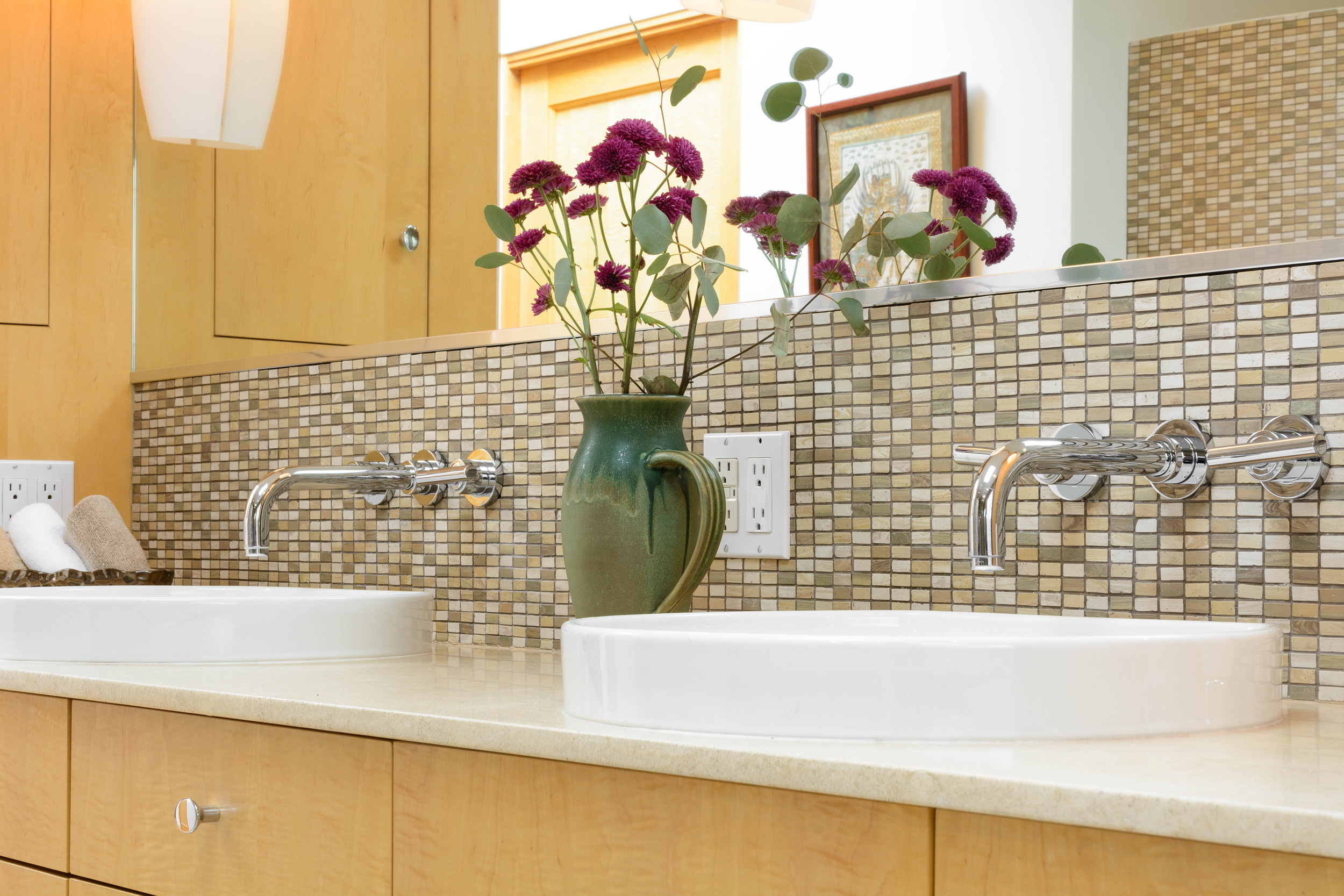 Master bathroom white double vessel sinks with sleek wall-mounted widespread faucets on mosaic tile backsplash