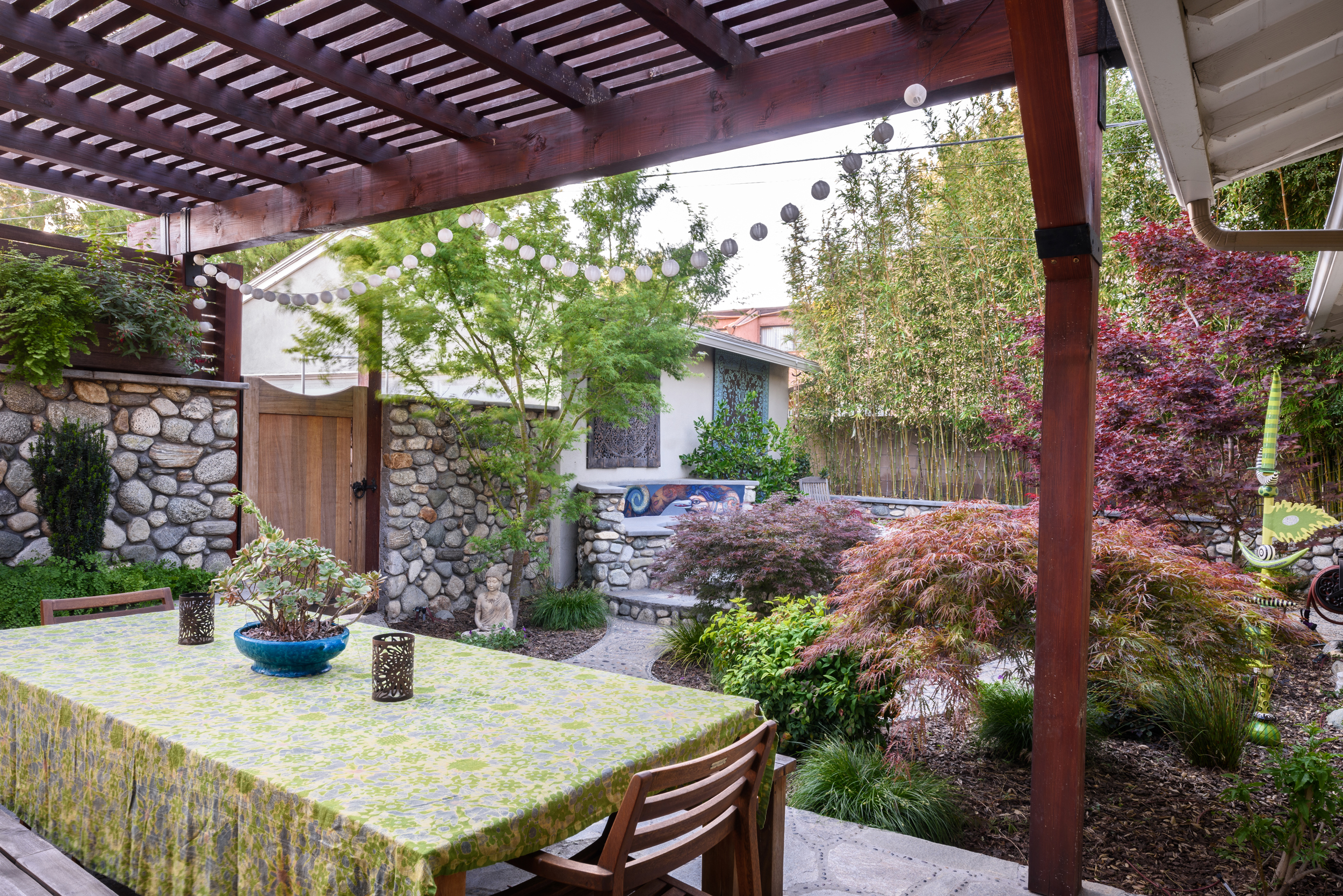 Wood pergola hand-rubbed oil finished providing for an outdoor dining area giving onto a serene Asian-inspired woodland backyard
