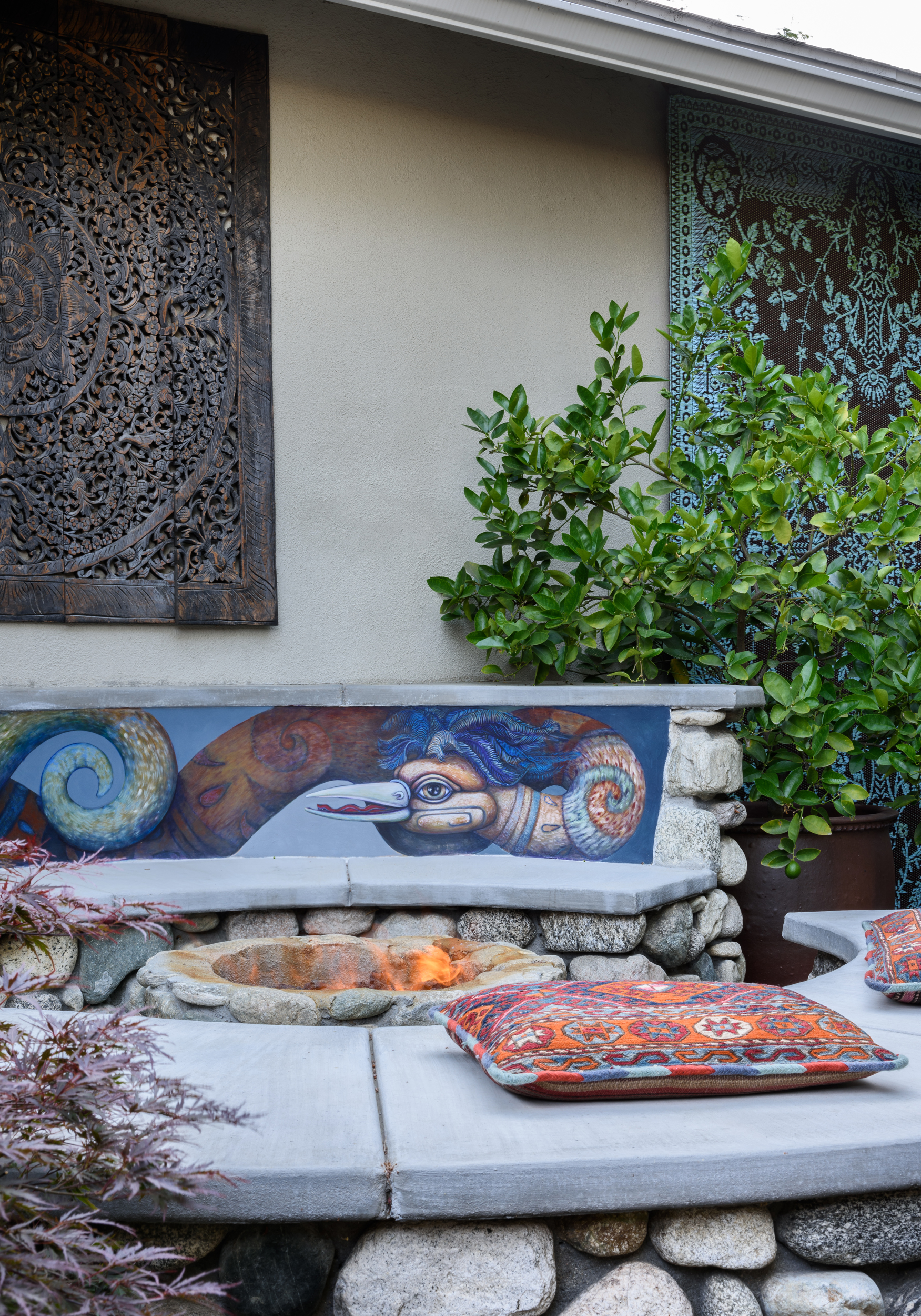 Serene Asian-inspired woodland backyard with a stone fire pit seating area showcasing artwork