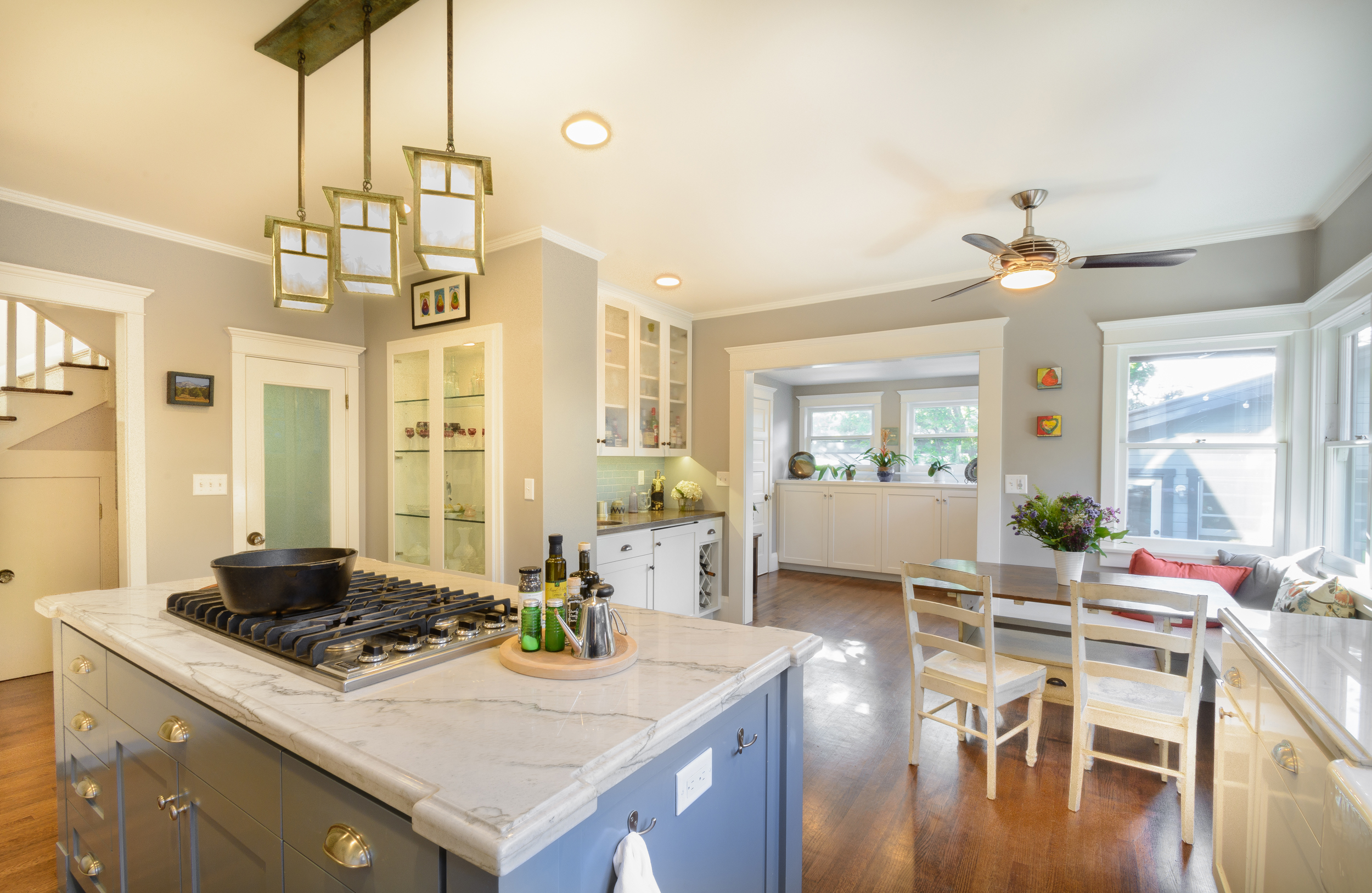 This craftsman style kitchen features a neutral color palette, wood floor, craftsman light fixtures, glass door display pantry cabinets, a breakfast nook and a bar area