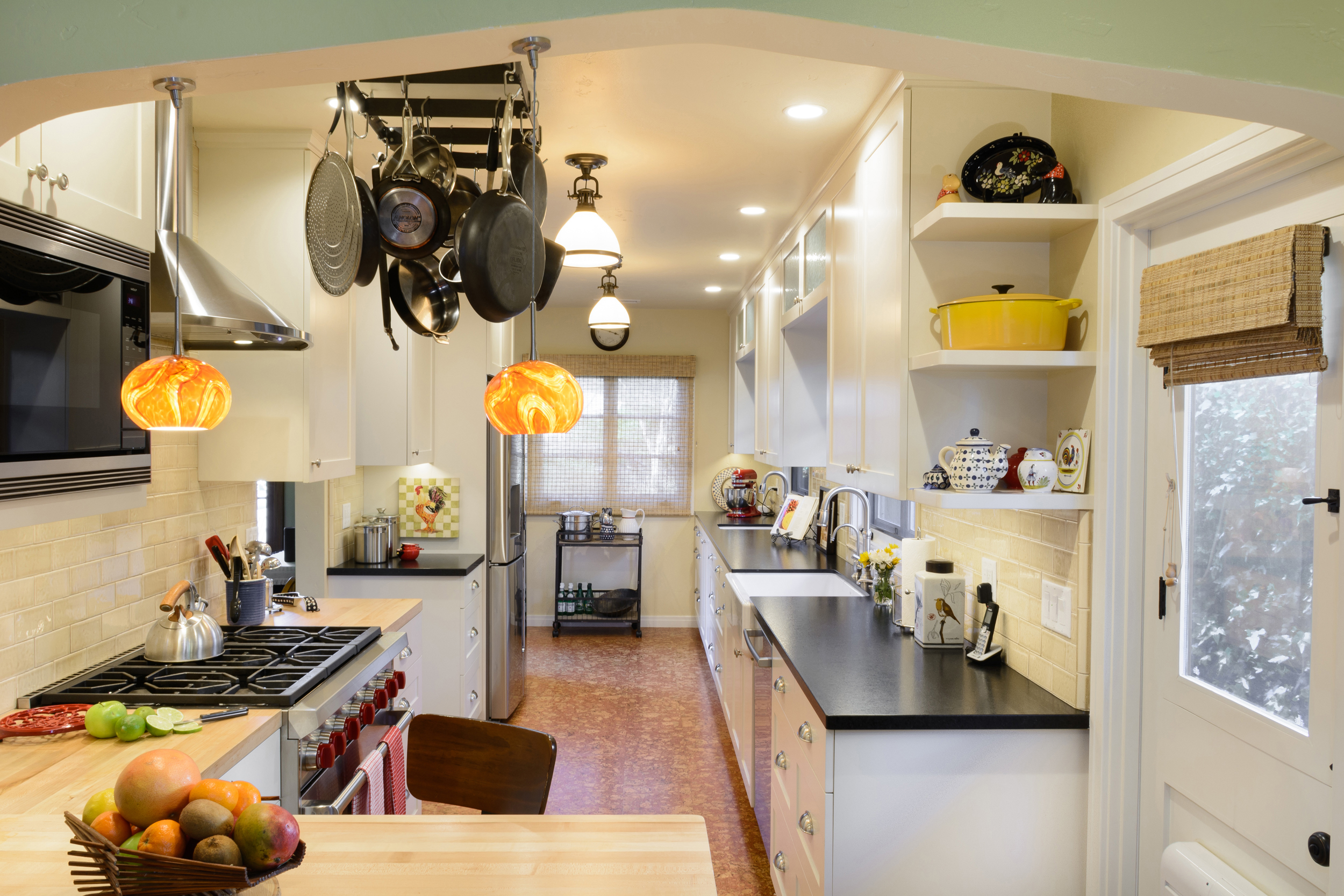 Colorful and warm old world charm galley kitchen with white Shaker cabinets, cork flooring, wood and black leathered stone countertops, tile backsplash and peninsula with bar seating