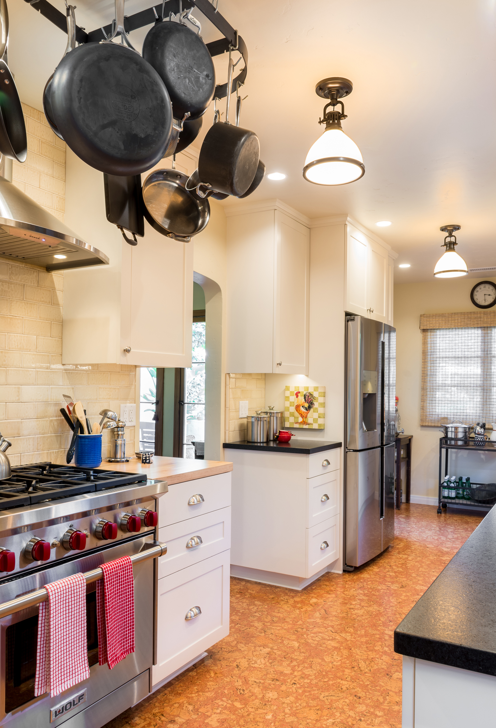 The range is a defining piece for a kitchen and, in this case, the hanging pot rack and accent light fixtures emphasize the old world style