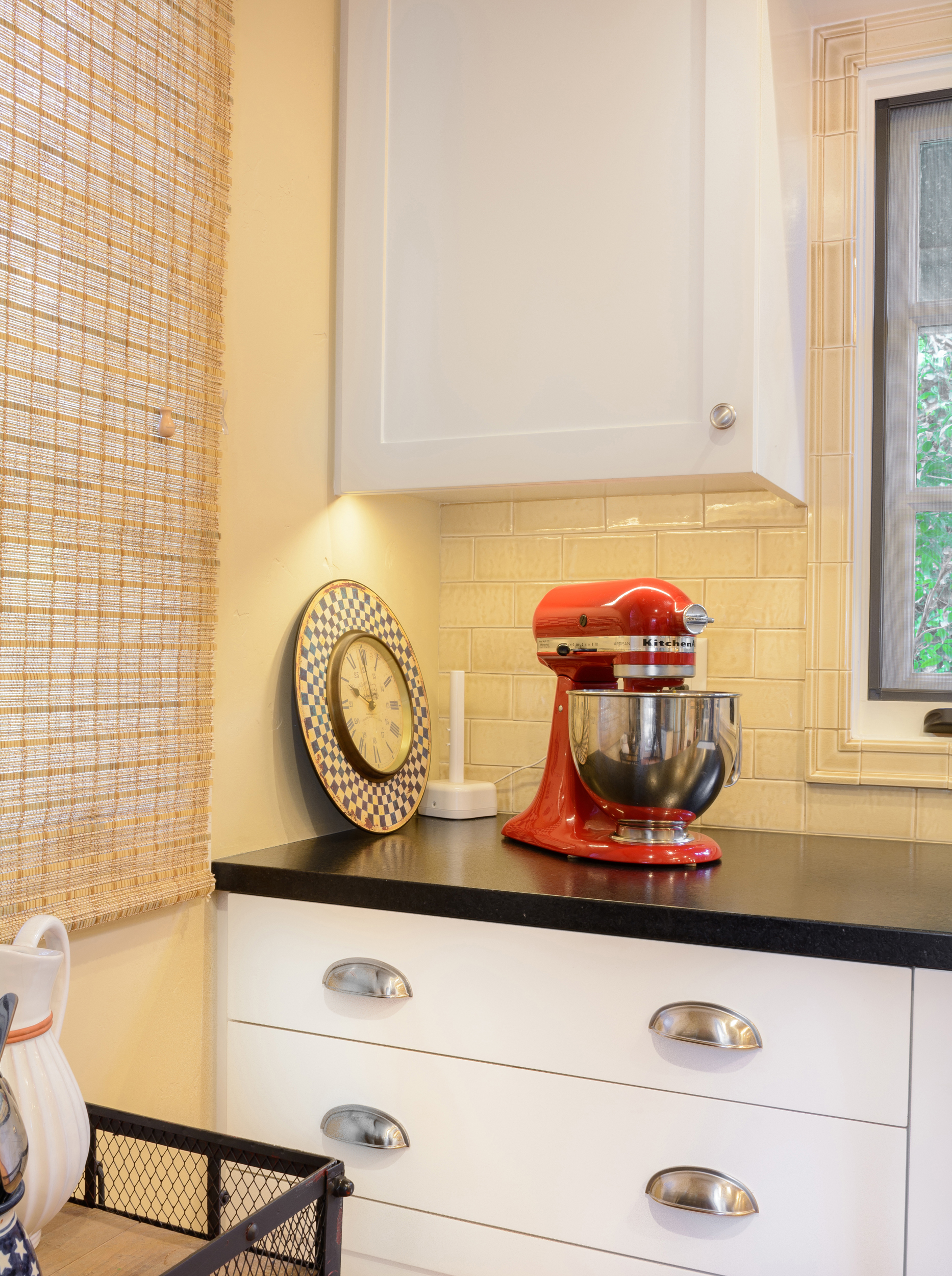 The red retro baking mixer and old clock add a hearty and colorful feel to the white Shaker cabinets with a black leathered stone top and tile backsplash