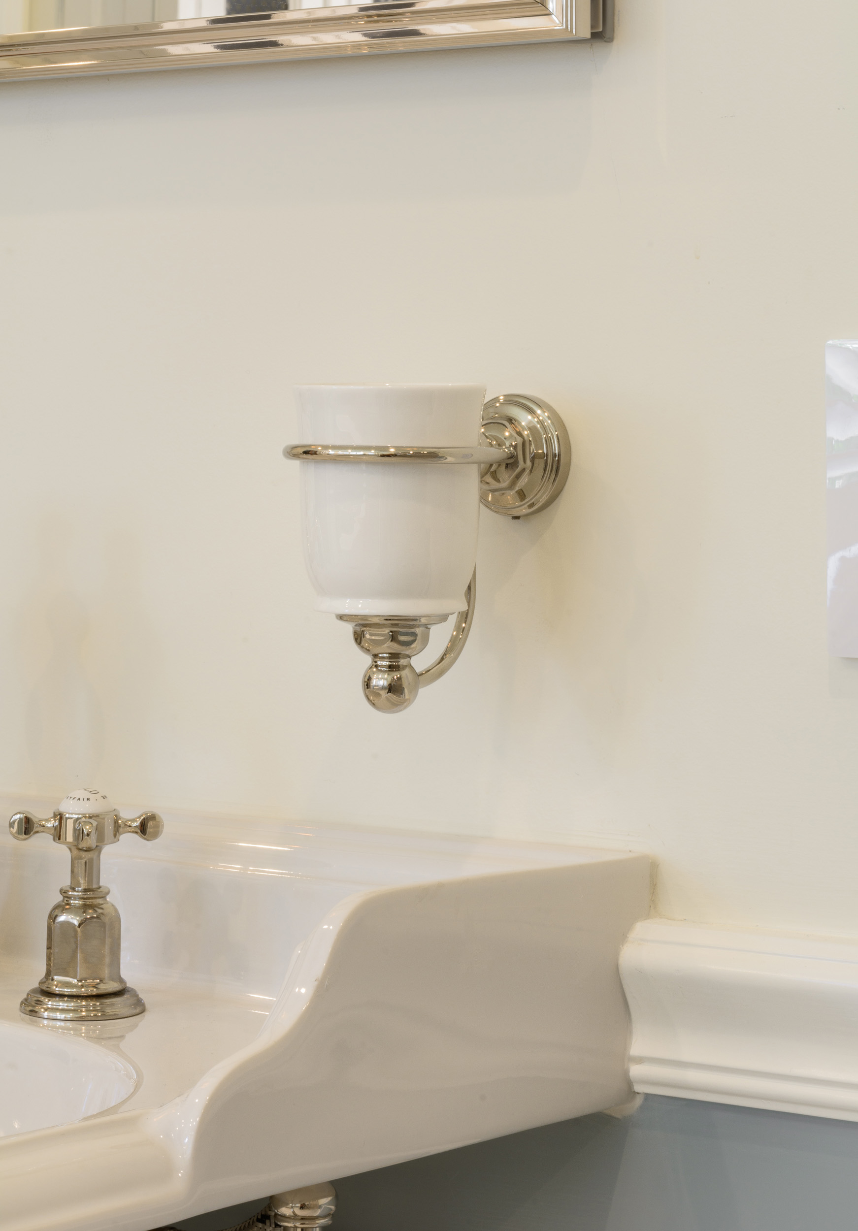 Polished nickel and white ceramic wall-mounted tumbler over console sink