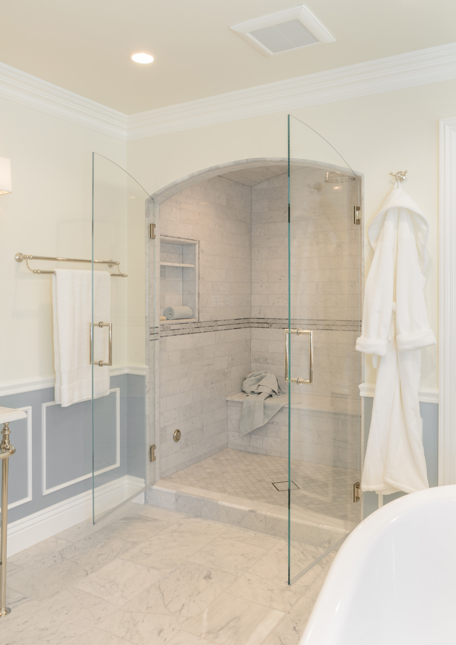 Low threshold shower alcove with frameless glass French swing shower doors
