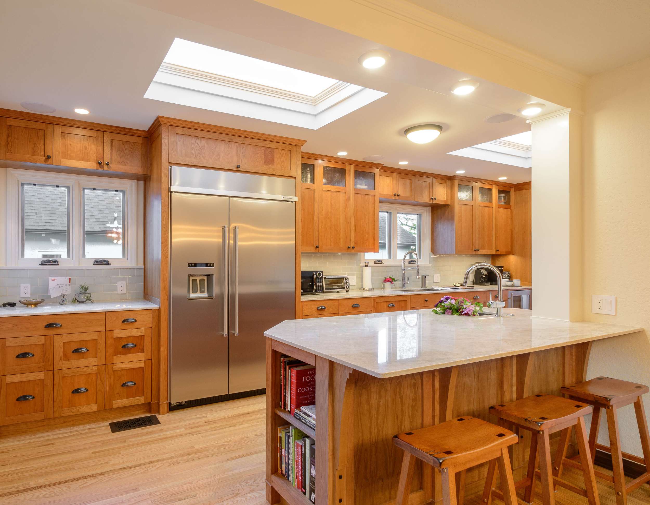 Impeccable lines and plenty of light for this Tudor kitchen remodel with custom-built cherry cabinets, accent hardware, oak floor, and a peninsula with a white stone countertop and bar seating area