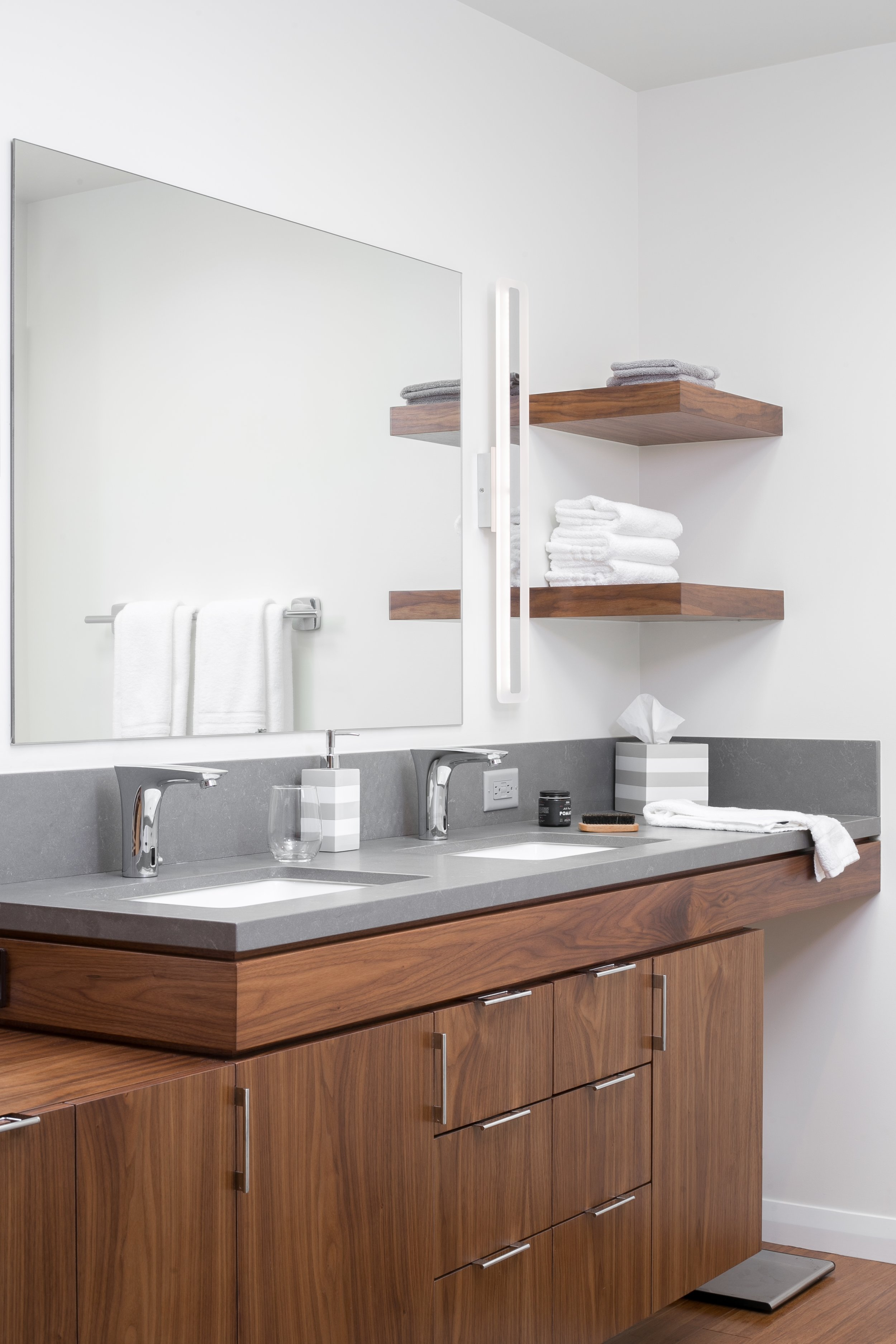 The minimalism and clean lines of the walnut cabinetry, large mirror and wall sconces combine perfectly warmth and modern design