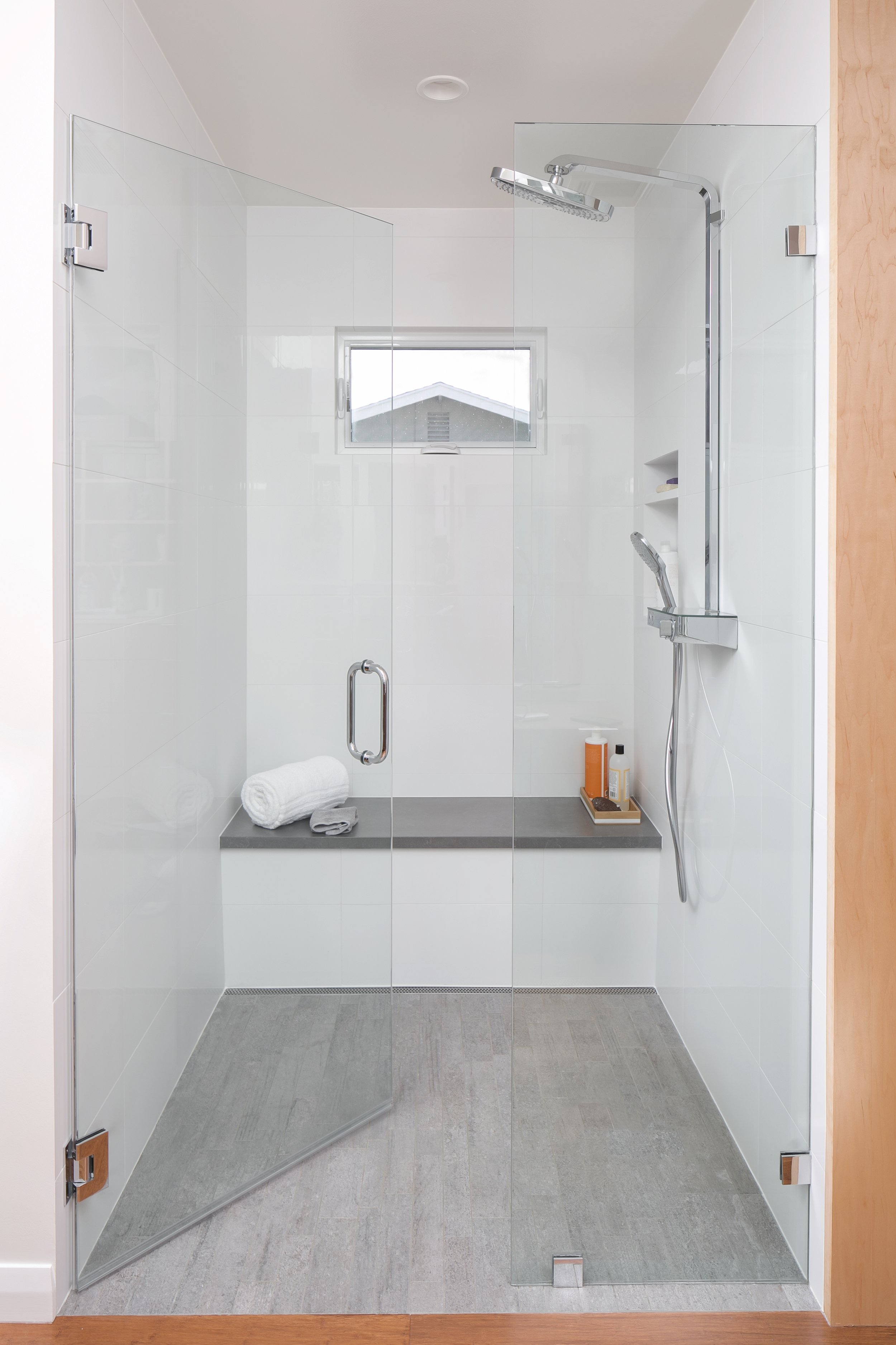 Walk-in shower design with plenty of light: white field tiles, light grey floor and bench top, small window, clear glass enclosure and sleek modern head and handheld combo faucet
