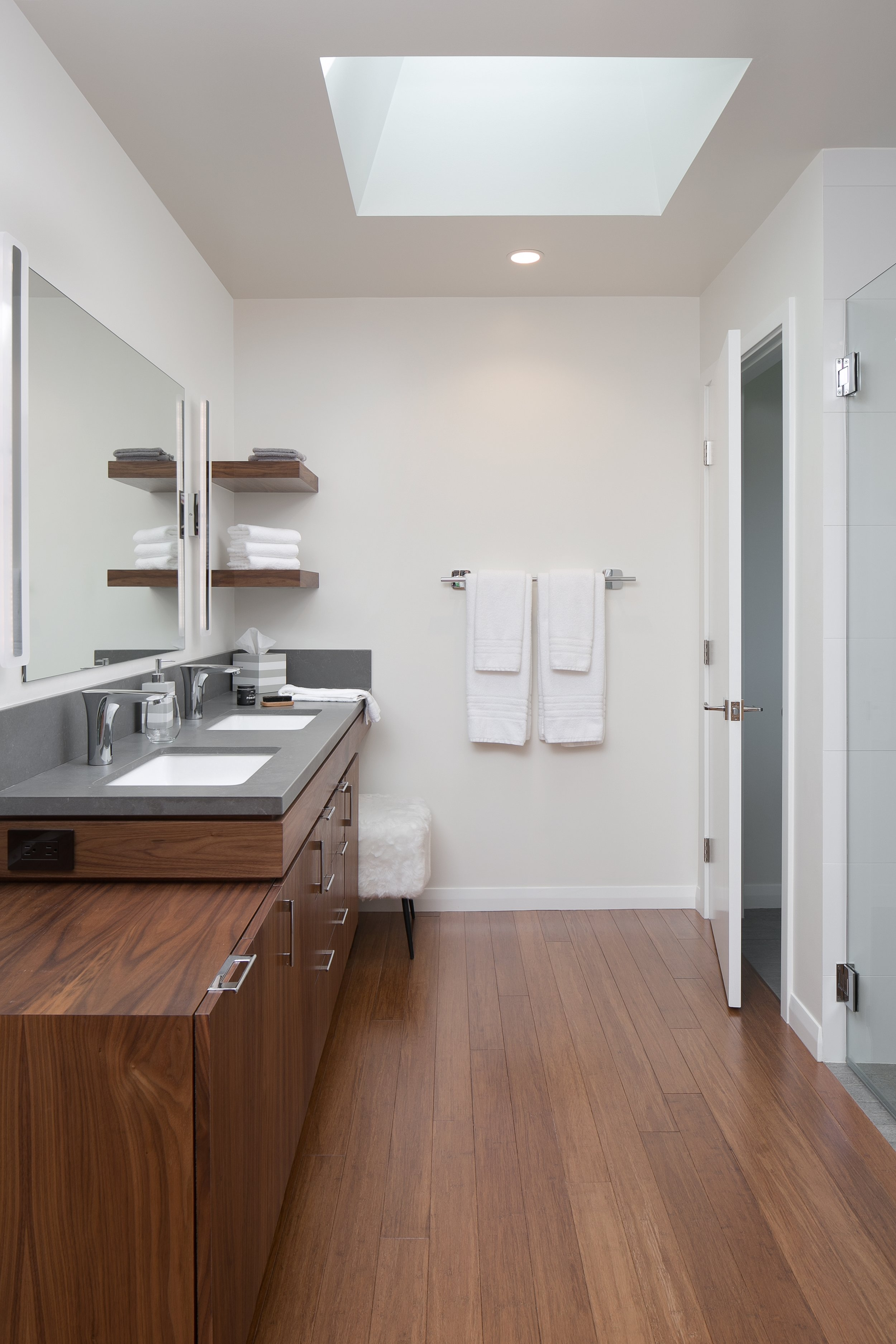 The skylight and white walls illuminate this contemporary ranch master bathroom finished with bamboo flooring and custom walnut cabinetry