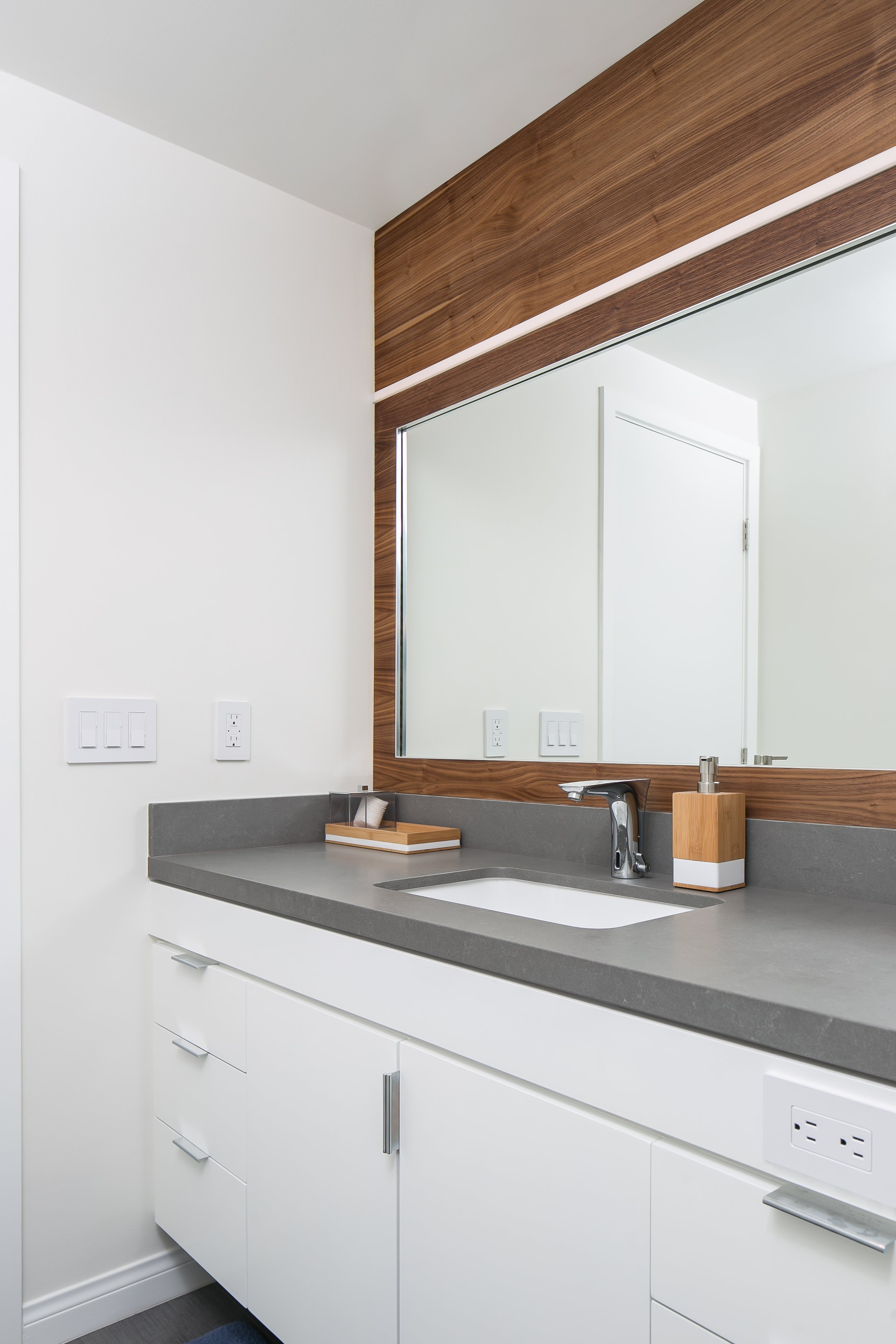 Large mirror with walnut surround and modern lighting atop white vanity with grey counter