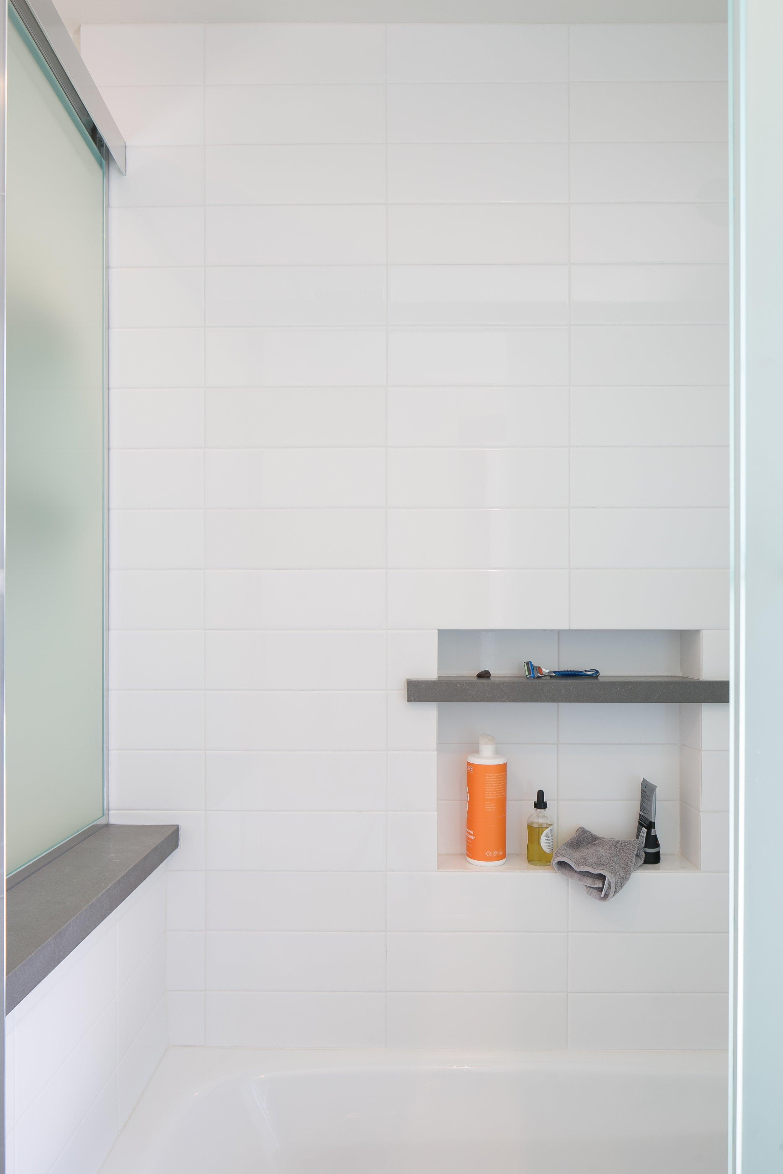 Bathtub niche: white gloss tiles and a grey matte contrasting stone