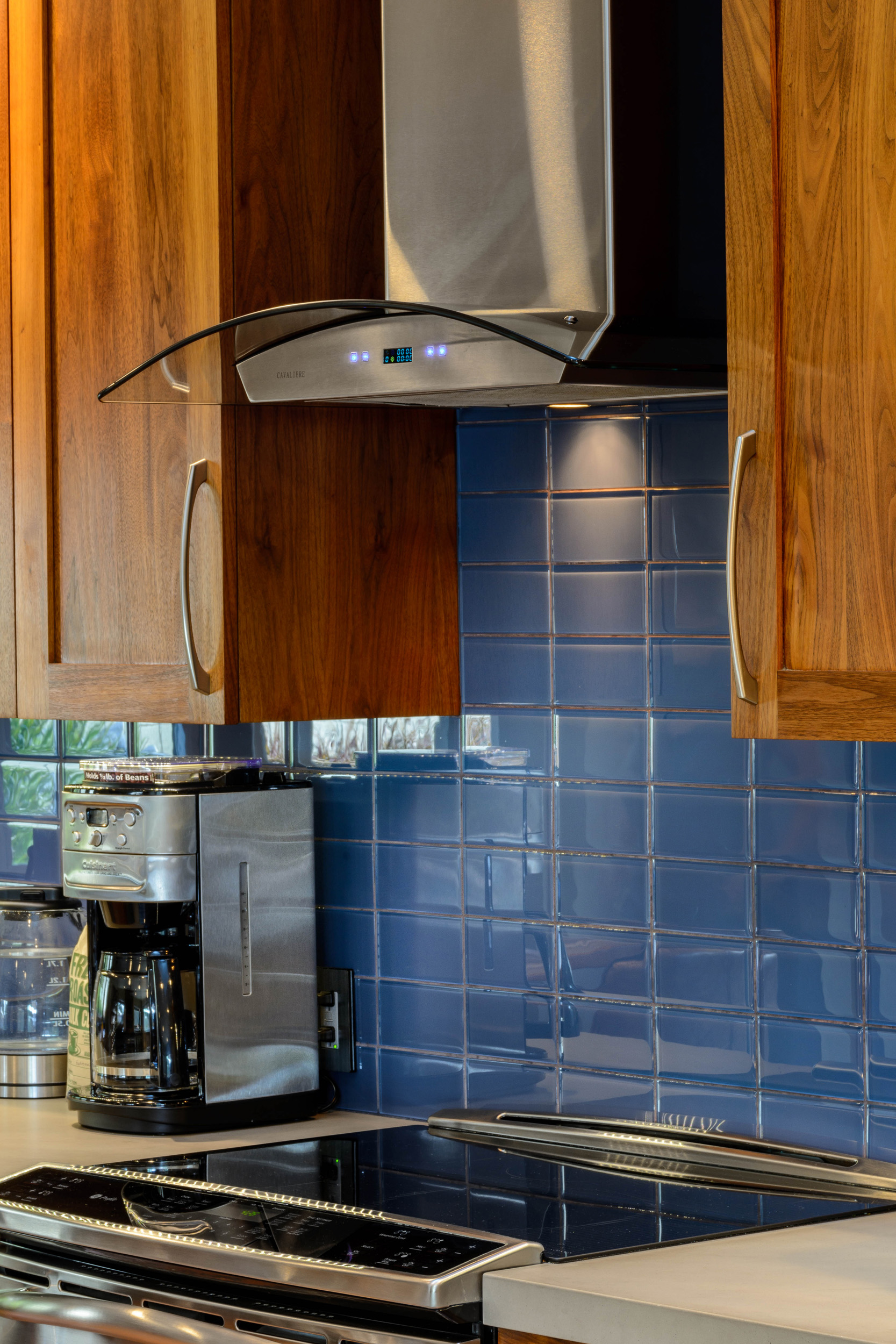 Electric range top with a sleek stainless steel wall-mounted hood and a dark blue glass tile backsplash