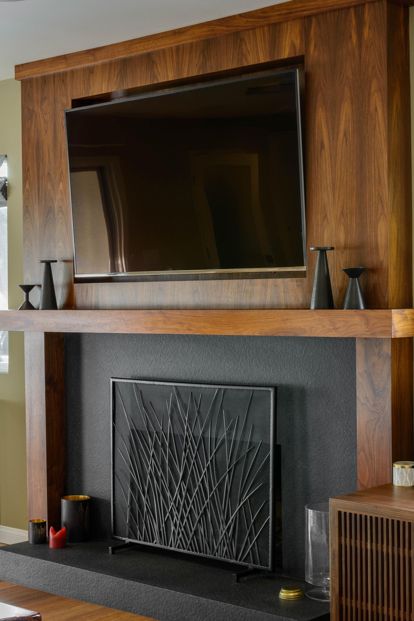 TV niche within a custom-built walnut fireplace surround